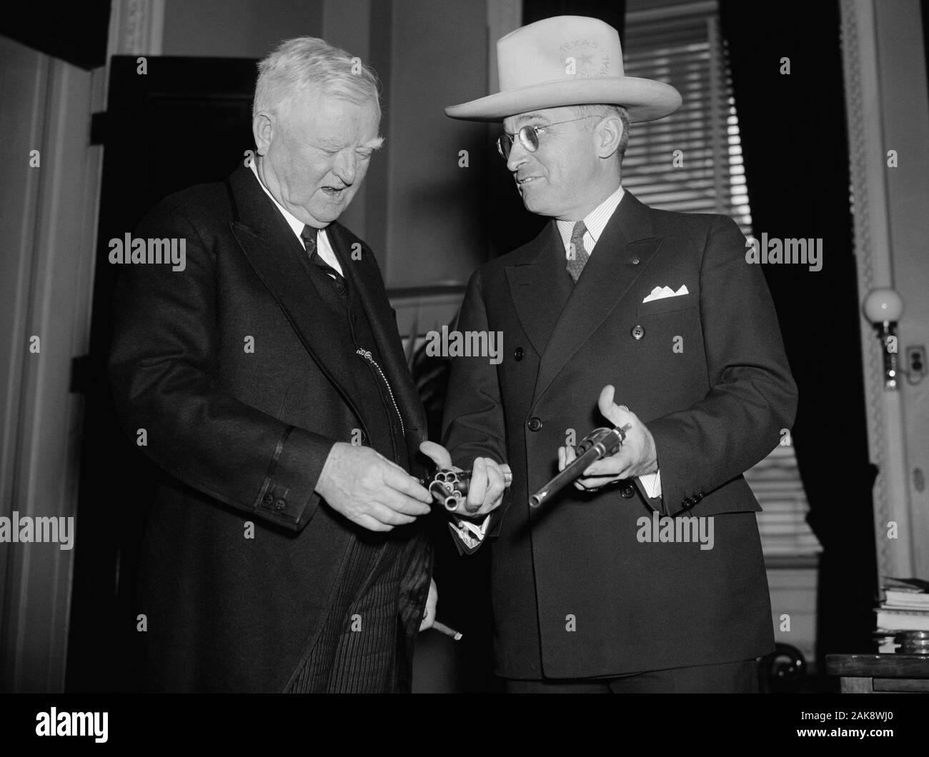 Vintage photo of US Vice President John Nance Garner (left) being shown a pair of 45-caliber pistols by Missouri Senator - and future President - Harry S Truman. The guns were said to have been once owned by the notorious outlaw Jesse James and had been obtained by Truman from the wife of a doctor who had been given them by Jesse's brother Frank as payment for medical services. Photo by Harris & Ewing taken in Washington DC on February 17 1938. Garner (1868 – 1967) was the 32nd Vice President (1933 – 1941) and Truman (1884 – 1972) would later become the 33rd US President (1945 – 1953). Stock Photo