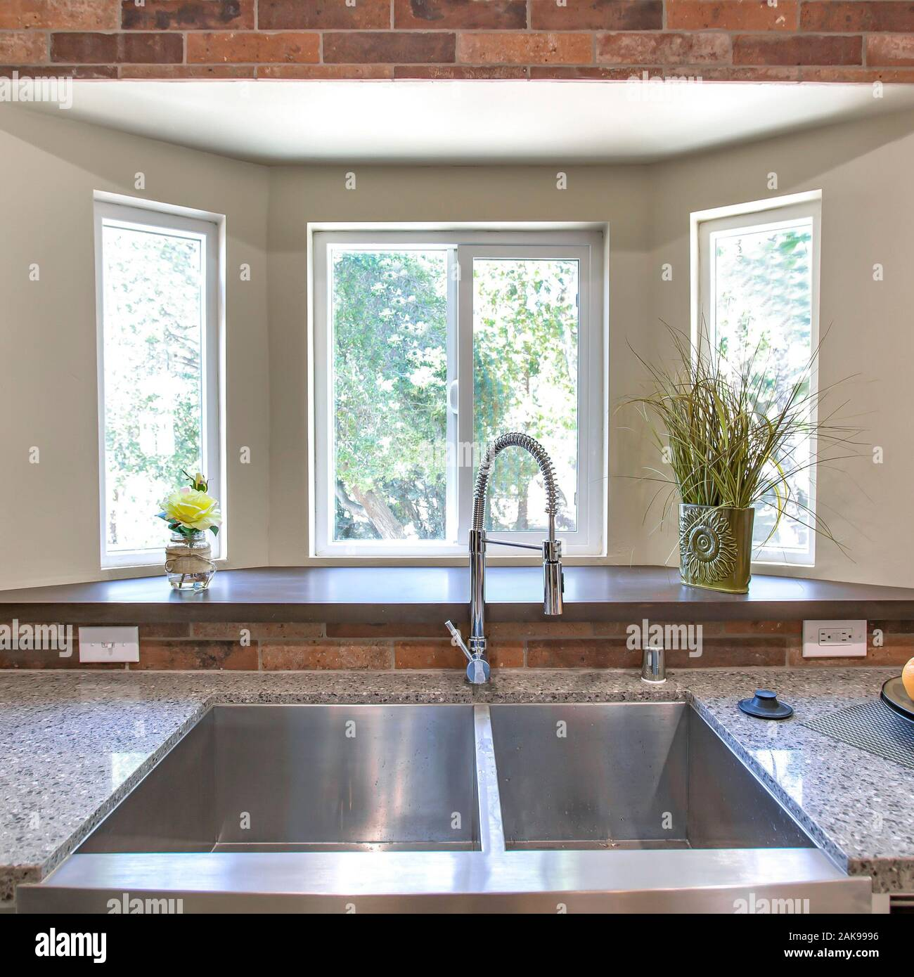 Square Kitchen sink close up with bay windows in the background Stock Photo