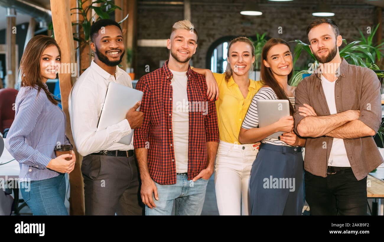 Group of young successful team of designers posing to camera in office, panorama Stock Photo