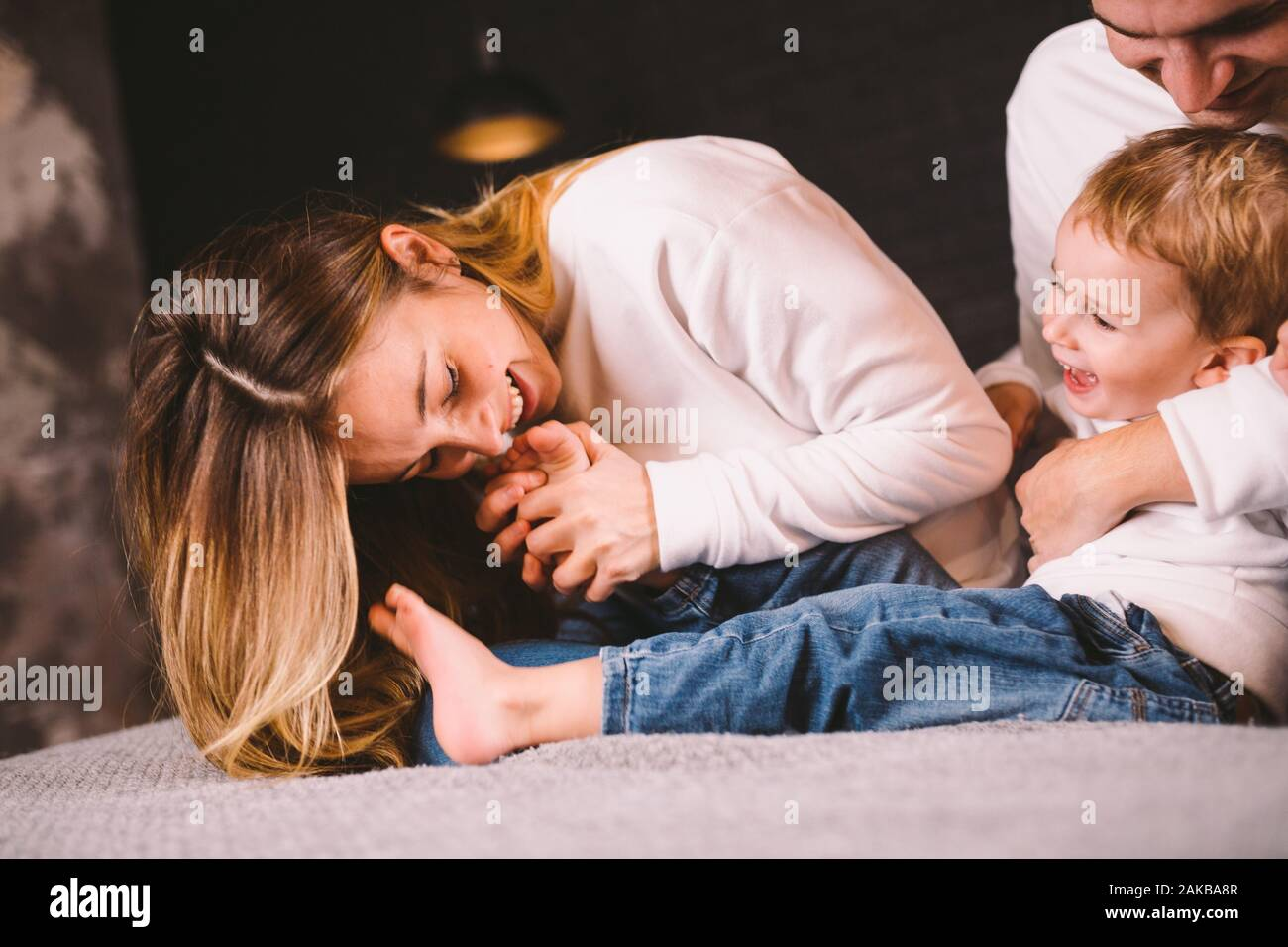 Happy family having fun lying down on bed at home. Happy Family In Bed. Mom dad and son lie on bedroom at within doors. father, mother and child Stock Photo