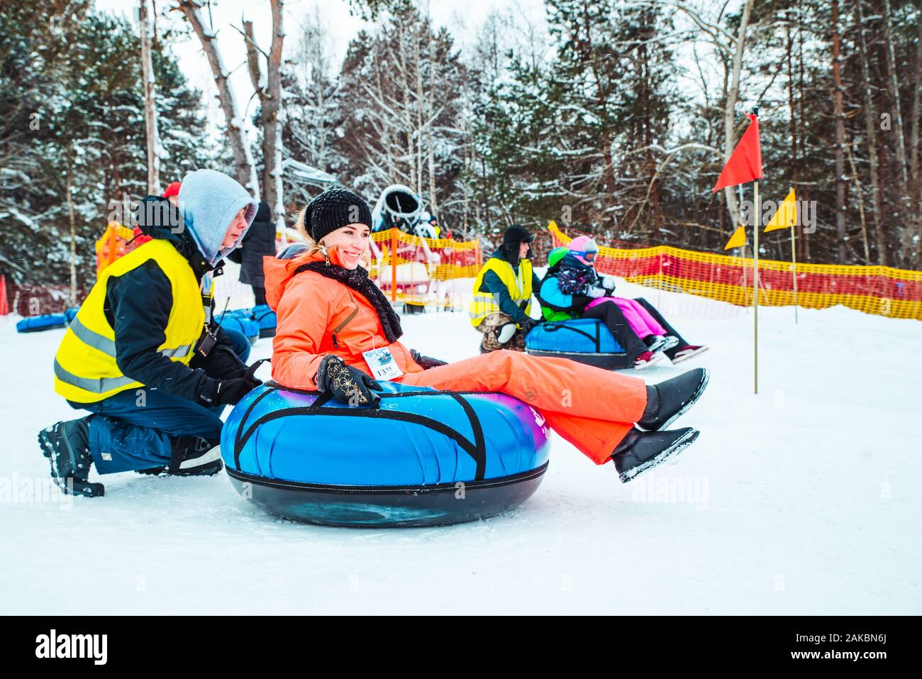 LVIV, UKRAINE - January 7, 2019: family ride down by snowing hill with snow tube Stock Photo
