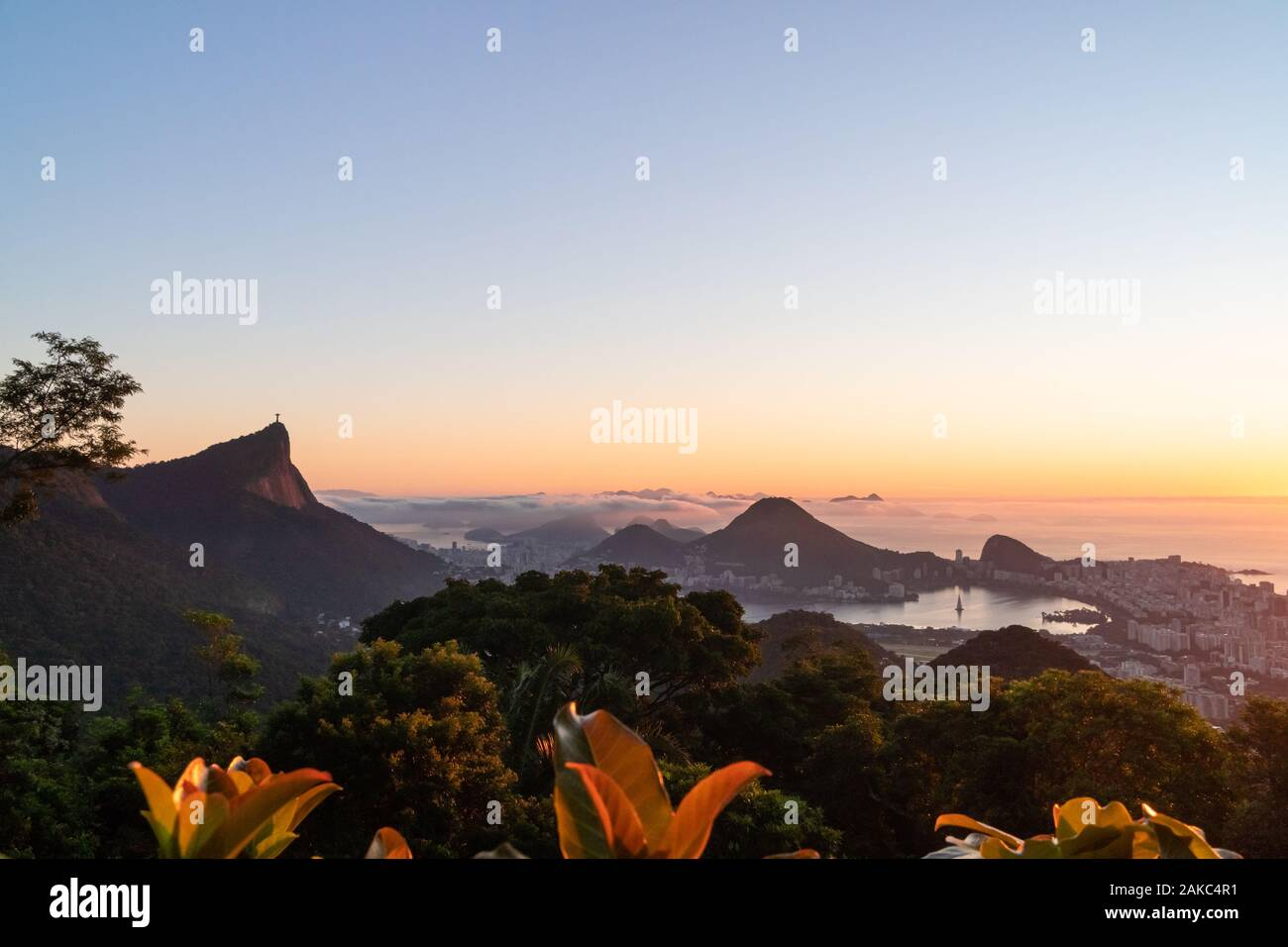 Sunrise over the city of Rio de Janeiro,Sugarloaf and Christ the Redeemer statue from Vista Chinesa. Stock Photo