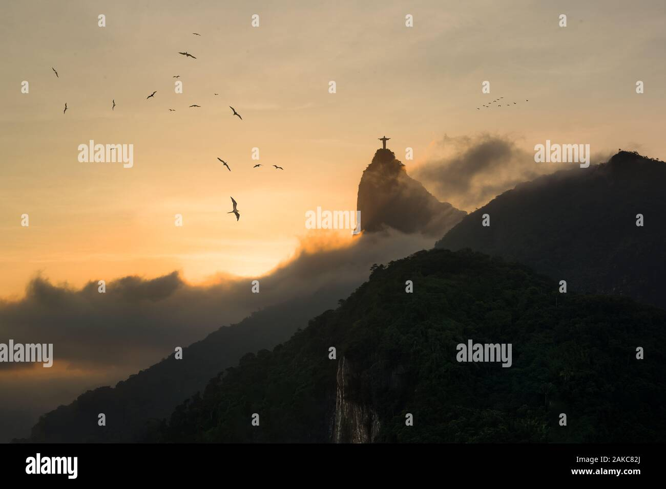 Sunset in Rio de Janeiro - Frigate Birds in sky with silhouette of Christ Redeemer rising from fog in background Stock Photo