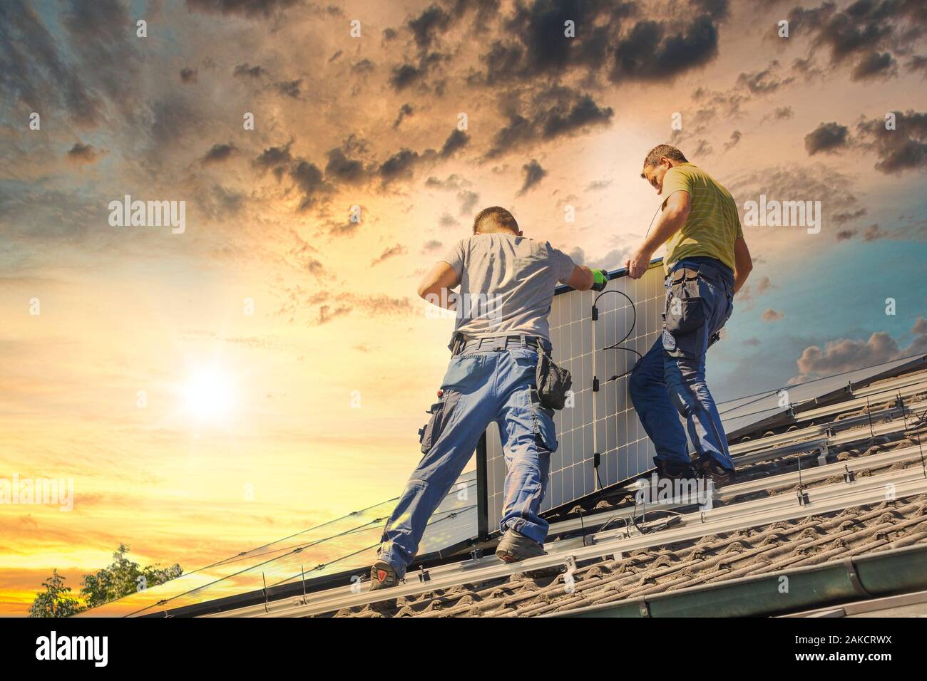 Installing solar photovoltaic panel system. Solar panel technician installing solar panels on roof. Alternative energy ecological concept. Stock Photo
