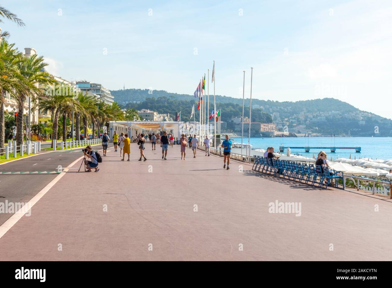 Joggers, walkers and photographers enjoy a summer day on the Promenade des Anglais at the resort city of Nice France on the Mediterranean Sea Stock Photo