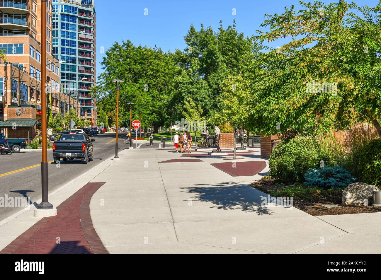 Pedestrians including a group of teens in bathing suits, walk towards McEuen Park during summer in the resort town of Coeur d'Alene, Idaho Stock Photo