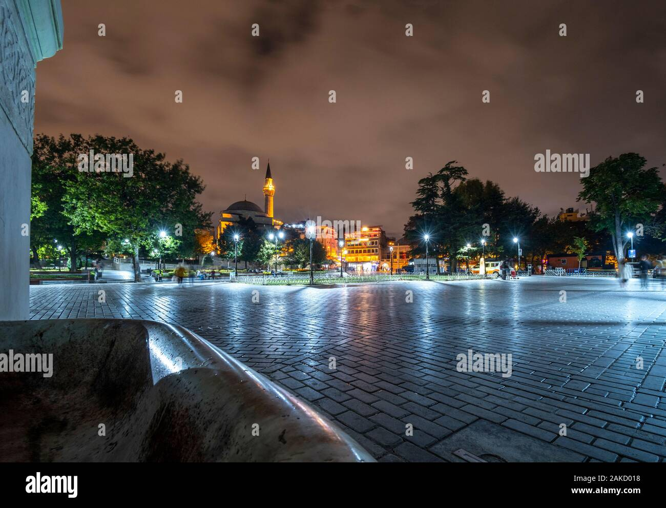Late night view from Sultanahmet Square as tourists pass by near an illuminated minaret and mosque in Istanbul, Turkey Stock Photo
