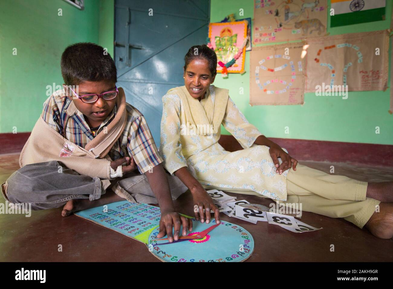 CAPTION: After-School Club (ASC) Coordinator Doddamma, who herself has rheumatoid arthritis, works on an activity designed under a visually impaired c Stock Photo