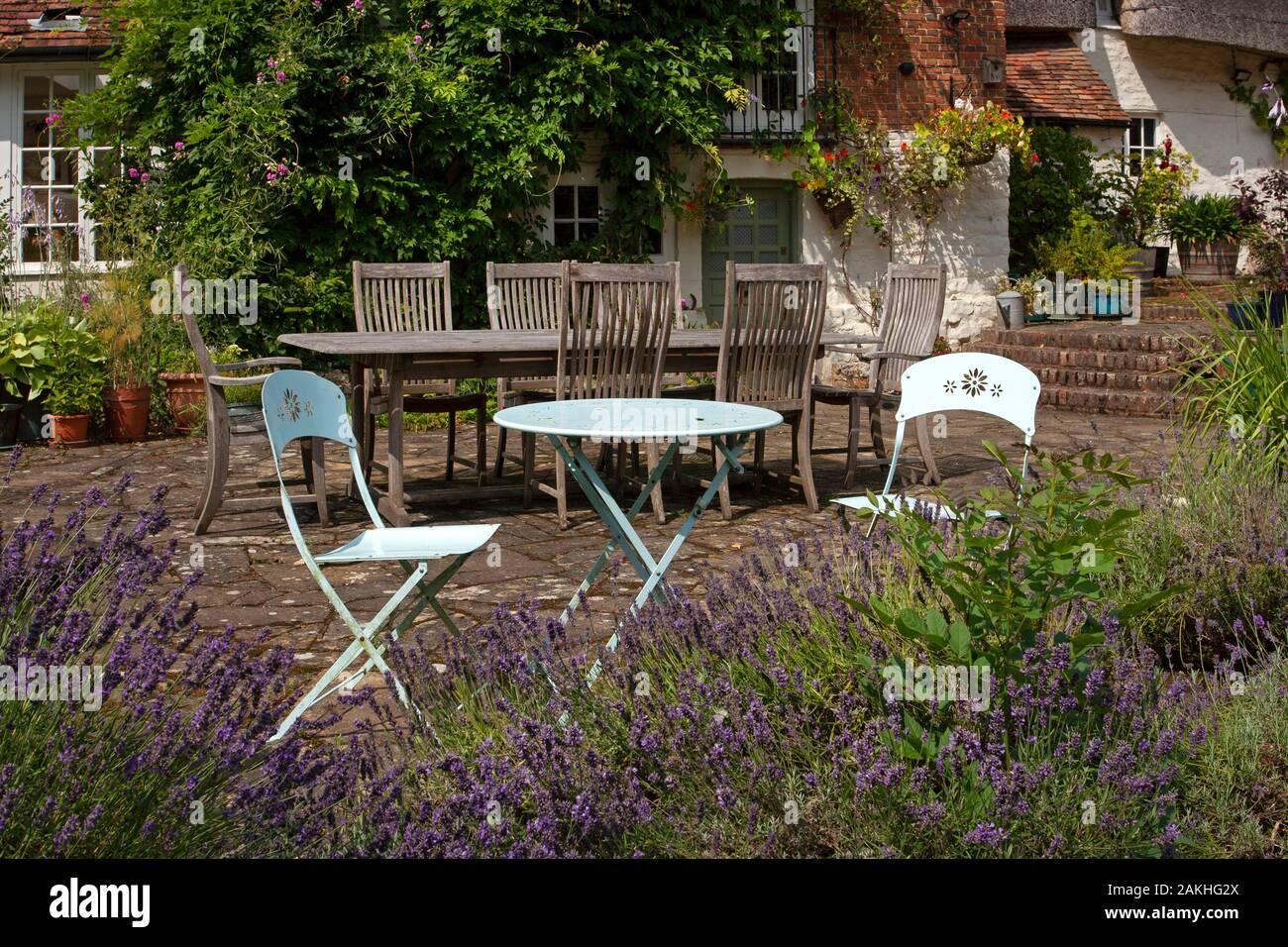 Metal Garden Seating Furniture On Stone Patio In English Summer Garden Stock Photo Alamy