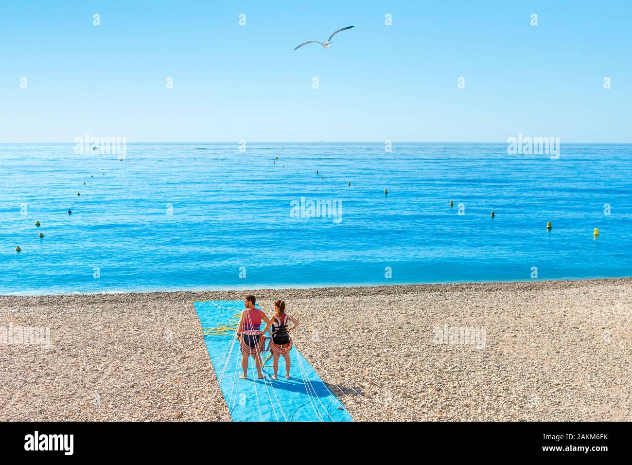 A young couple waits for a boat to being parasailing on the pebbly beach of the Bay of Angels on the French Riviera of the Mediterranean Sea. Stock Photo