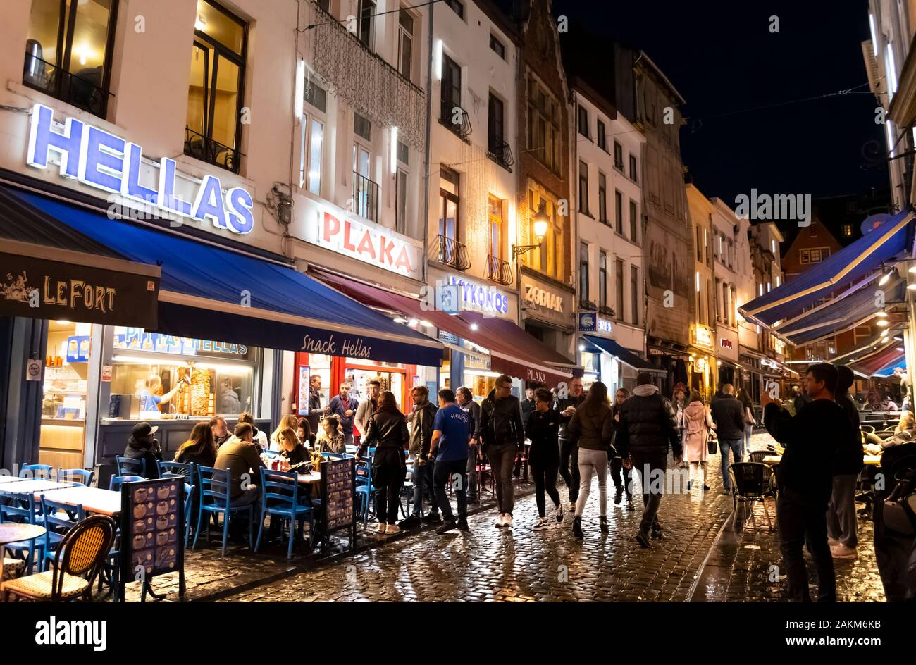 Greek cafes line the street in the historic old town of Brussels Belgium on a rainy late night in the busy, crowded urban center. Stock Photo