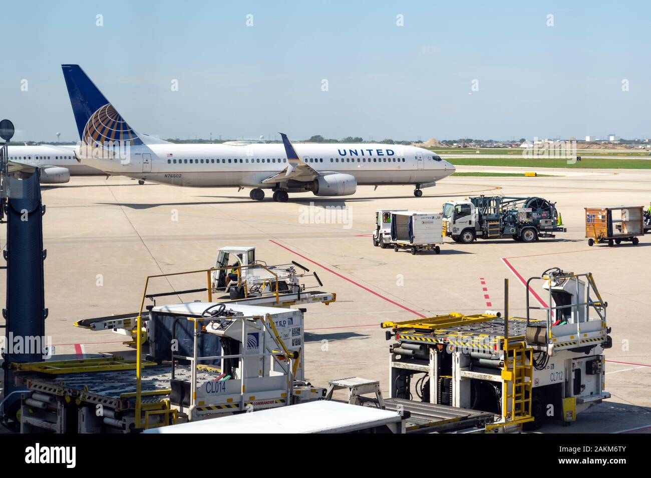 A united Airlines airplane prepares to take off from the tarmac at the Chicago O'Hare Airport as mechanical trucks fill the runway on a sunny day Stock Photo