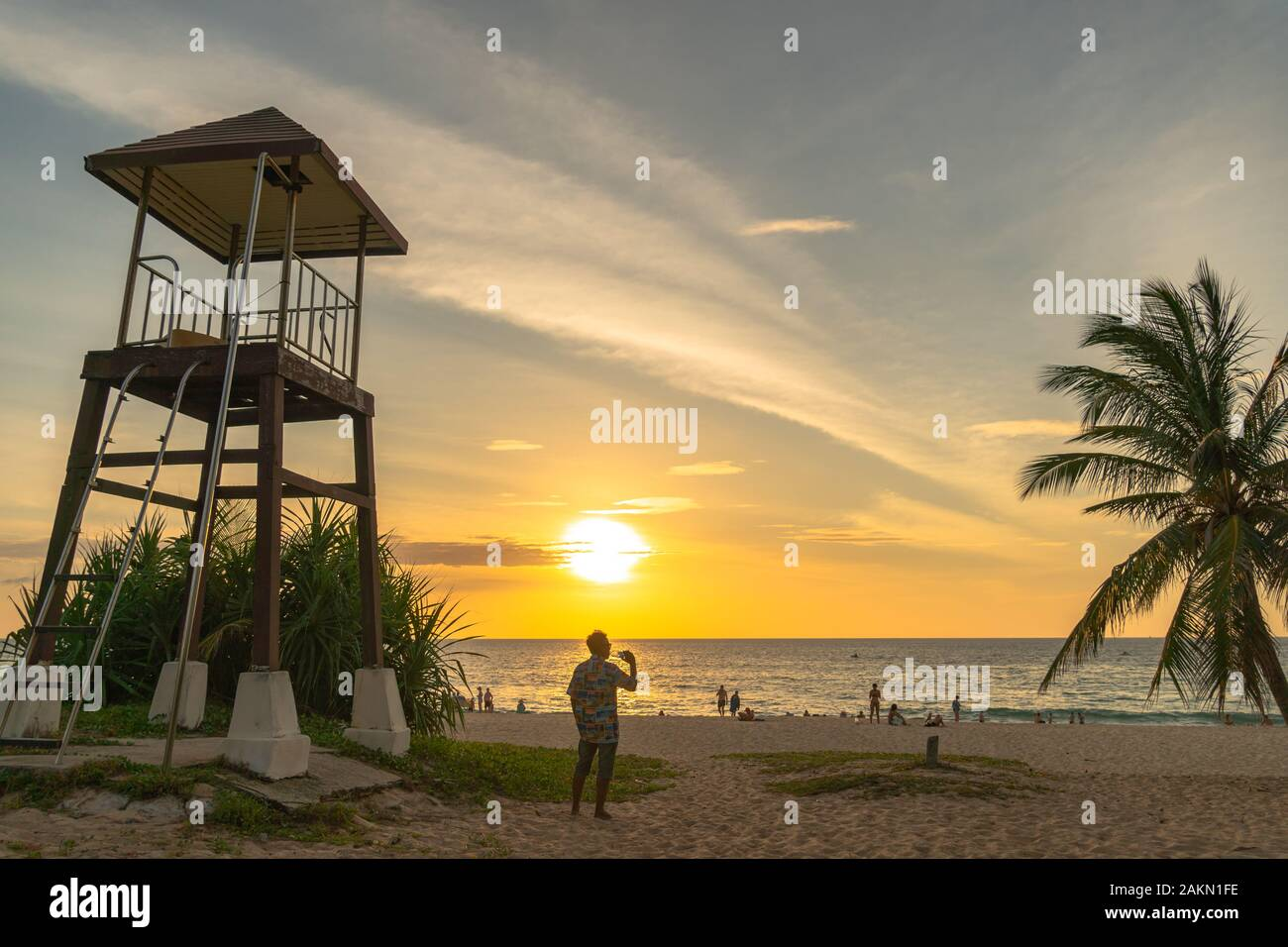 a man walking and take photo around lifegaurd tower during sunset at Karon beach Phuket Stock Photo