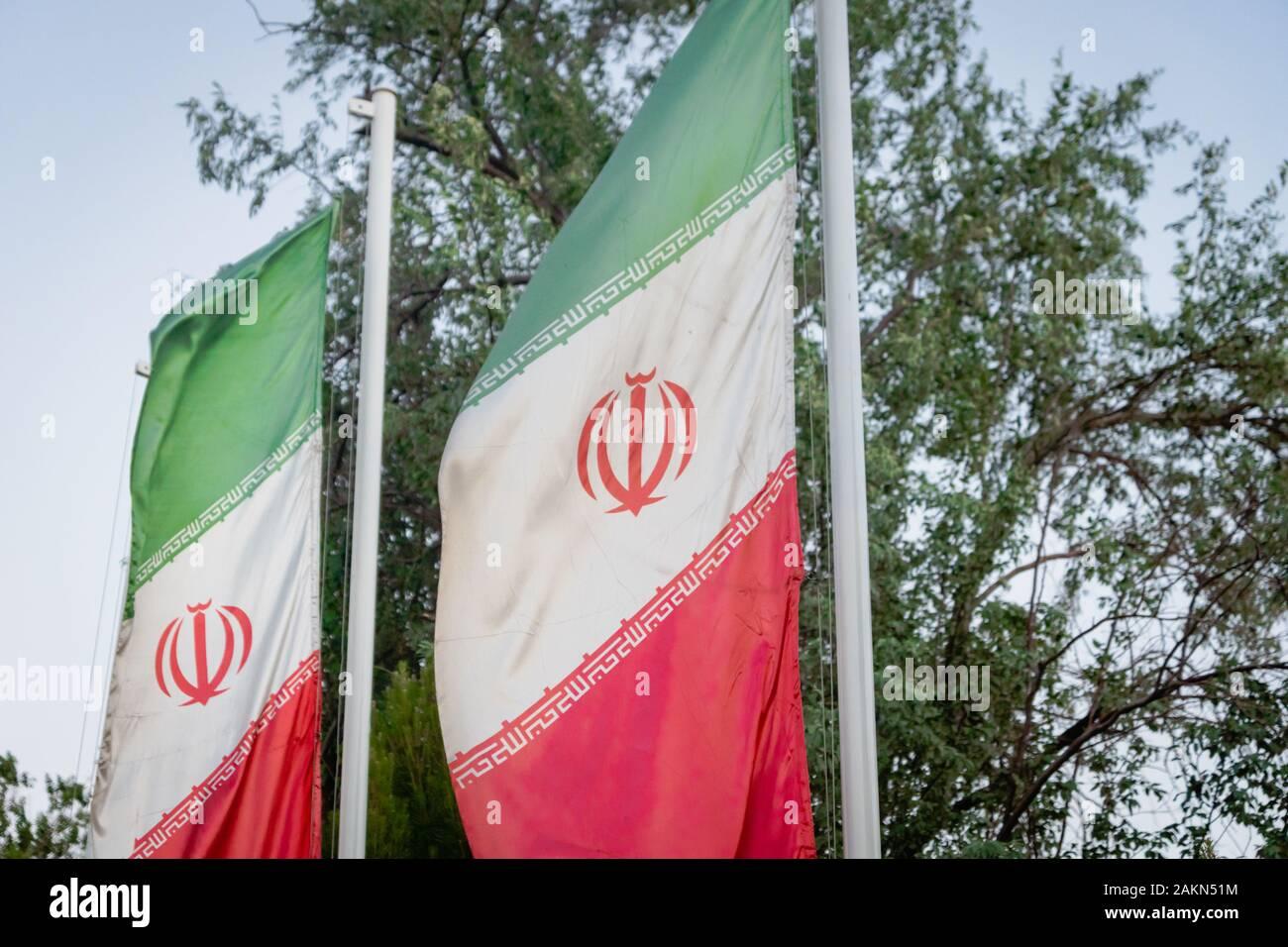 Iranian flags, flags of Islamic Republic of Iran, waving against blue sky Stock Photo