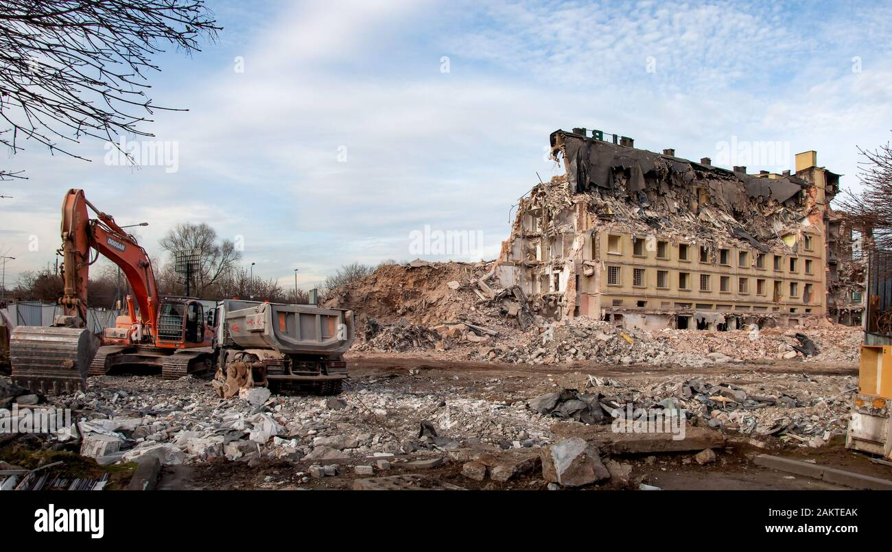 Kraków, Poland - December 17, 2019: Demolition of an old office building, called Elbud in a traditional way, using excavators, bulldozers and other de Stock Photo