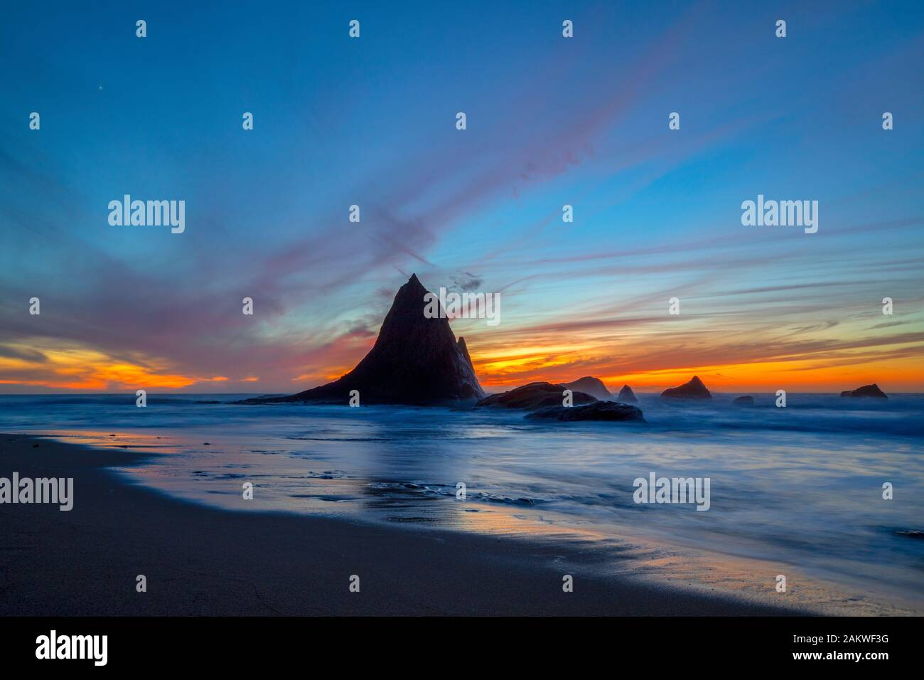 A colorful sunset backdrops the unique rock formations of Shark Fin Rock on Martin's Beach, in Half Moon Bay, California as the waves come in Stock Photo
