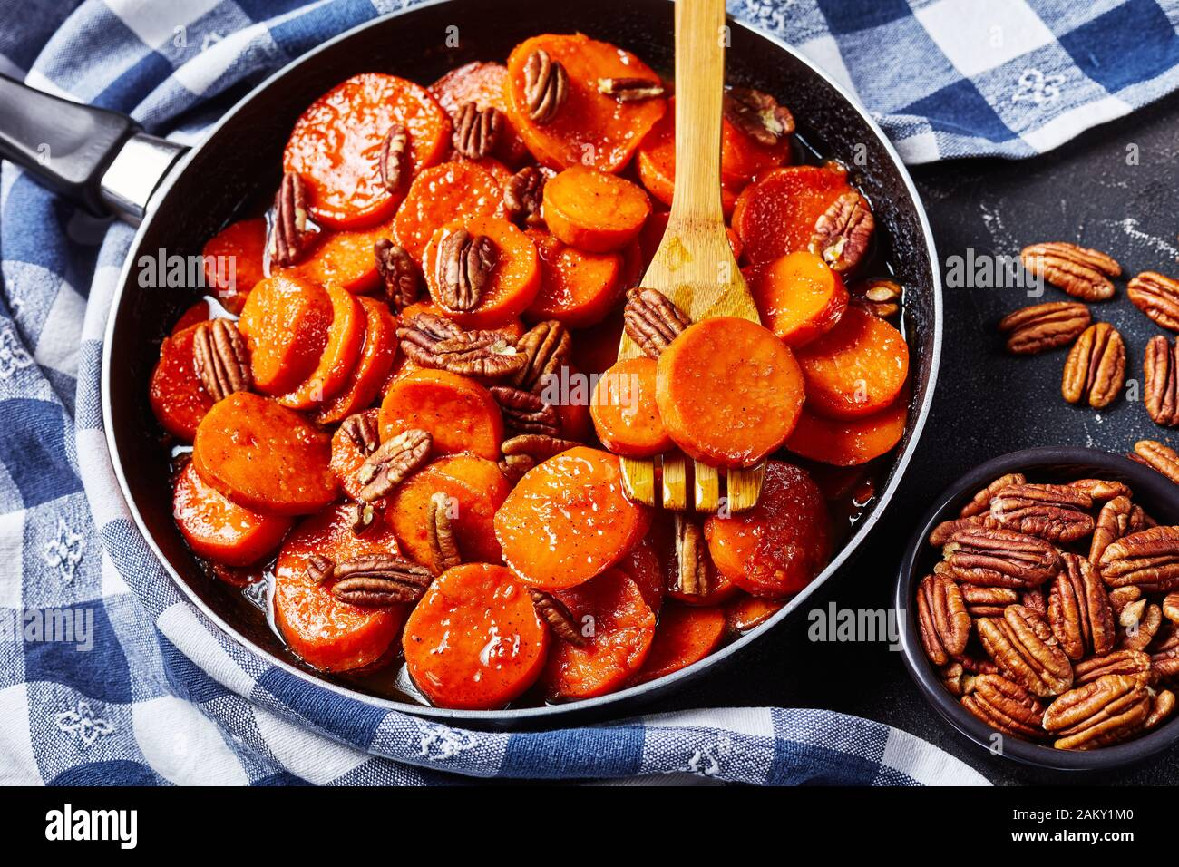 Candied sweet potatoes with brown sugar, maple syrup, orange juice and pecan nuts in a skillet on a concrete table with a kitchen towel, view from abo Stock Photo