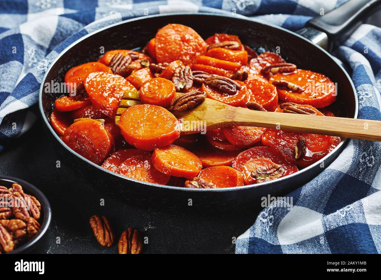 close-up of Candied sweet potatoes with brown sugar, maple syrup, orange juice and pecan nuts in a skillet with wooden spatula, view from above Stock Photo