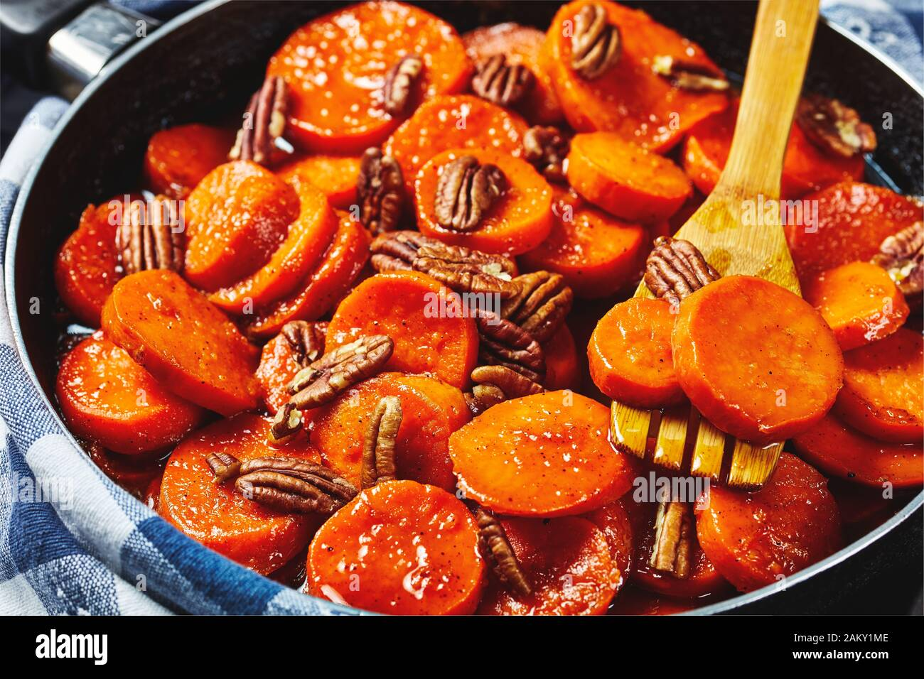 Candied sweet potatoes with brown sugar, maple syrup, orange juice and pecan nuts in a skillet with wooden spatula, view from above, close-up, macro Stock Photo