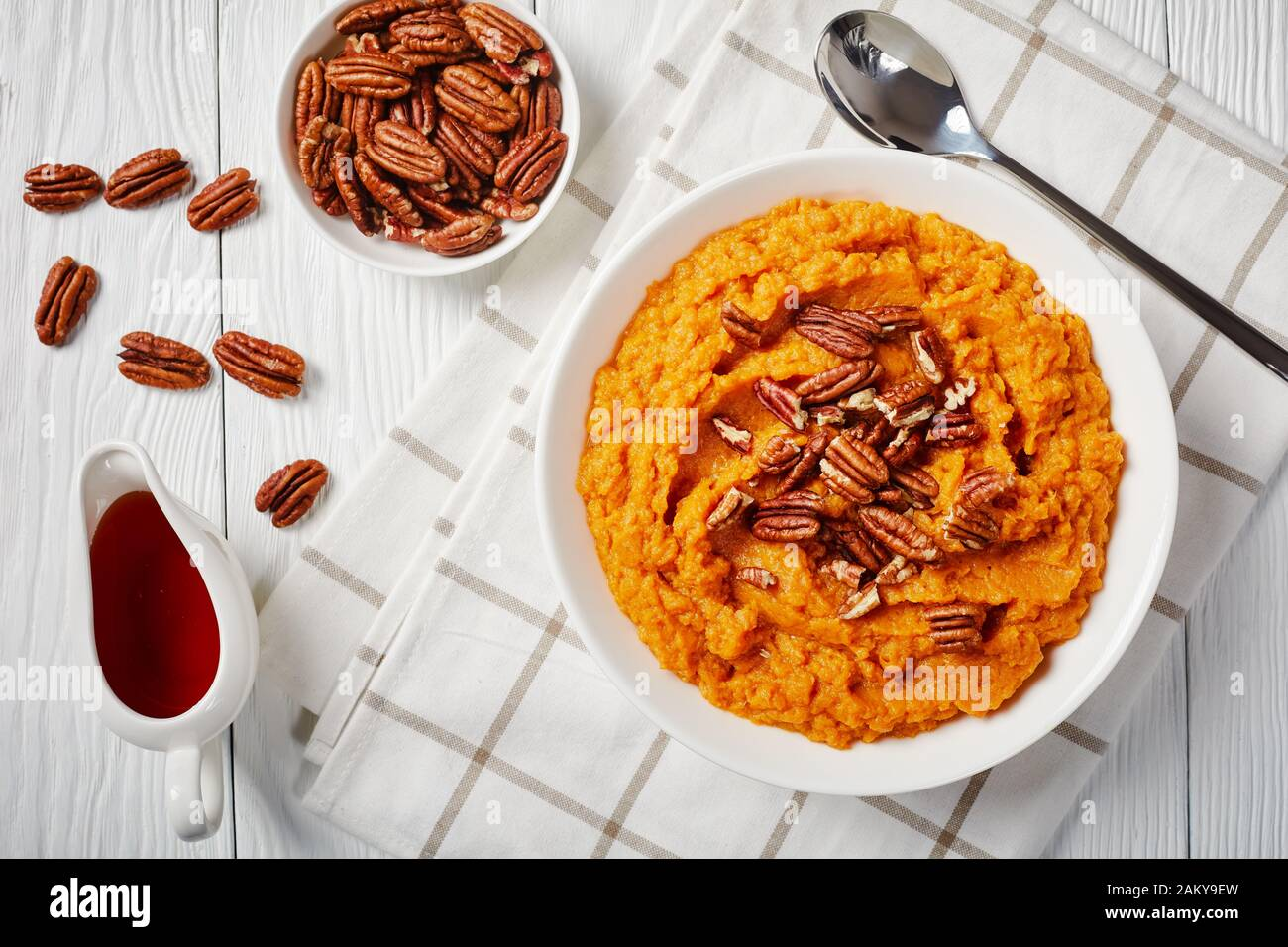 close-up of delicious mashed sweet potato topped with pecan nuts in a bowl. maple syrup in a white sauceboat on a wooden table, horizontal view from a Stock Photo