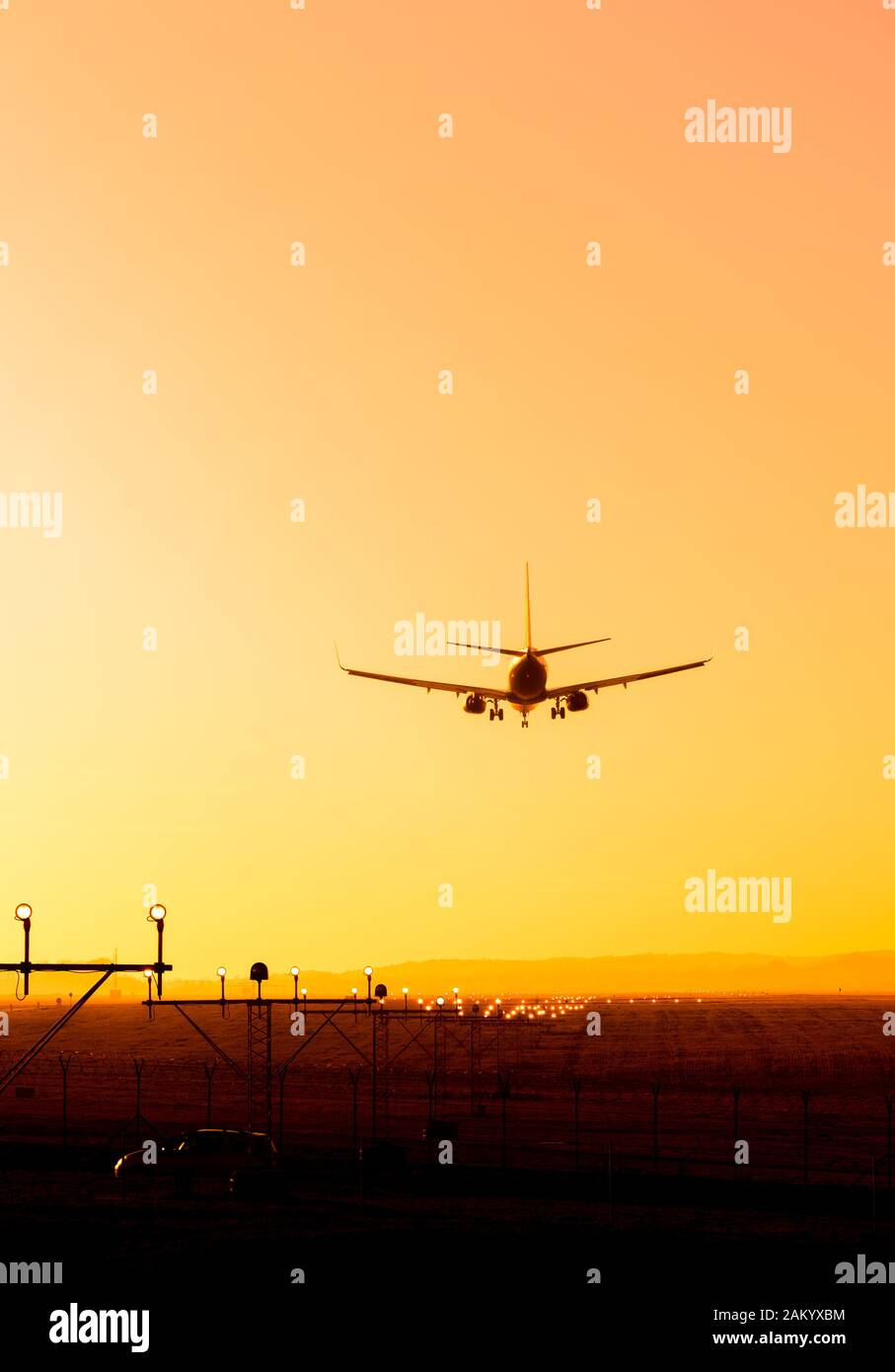 Back View Silhouette Of Airplane Landing At The Airport At Sunny Orange And Purple Sunset Runway End Identification Lights And Strobe Glowing Stock Photo Alamy