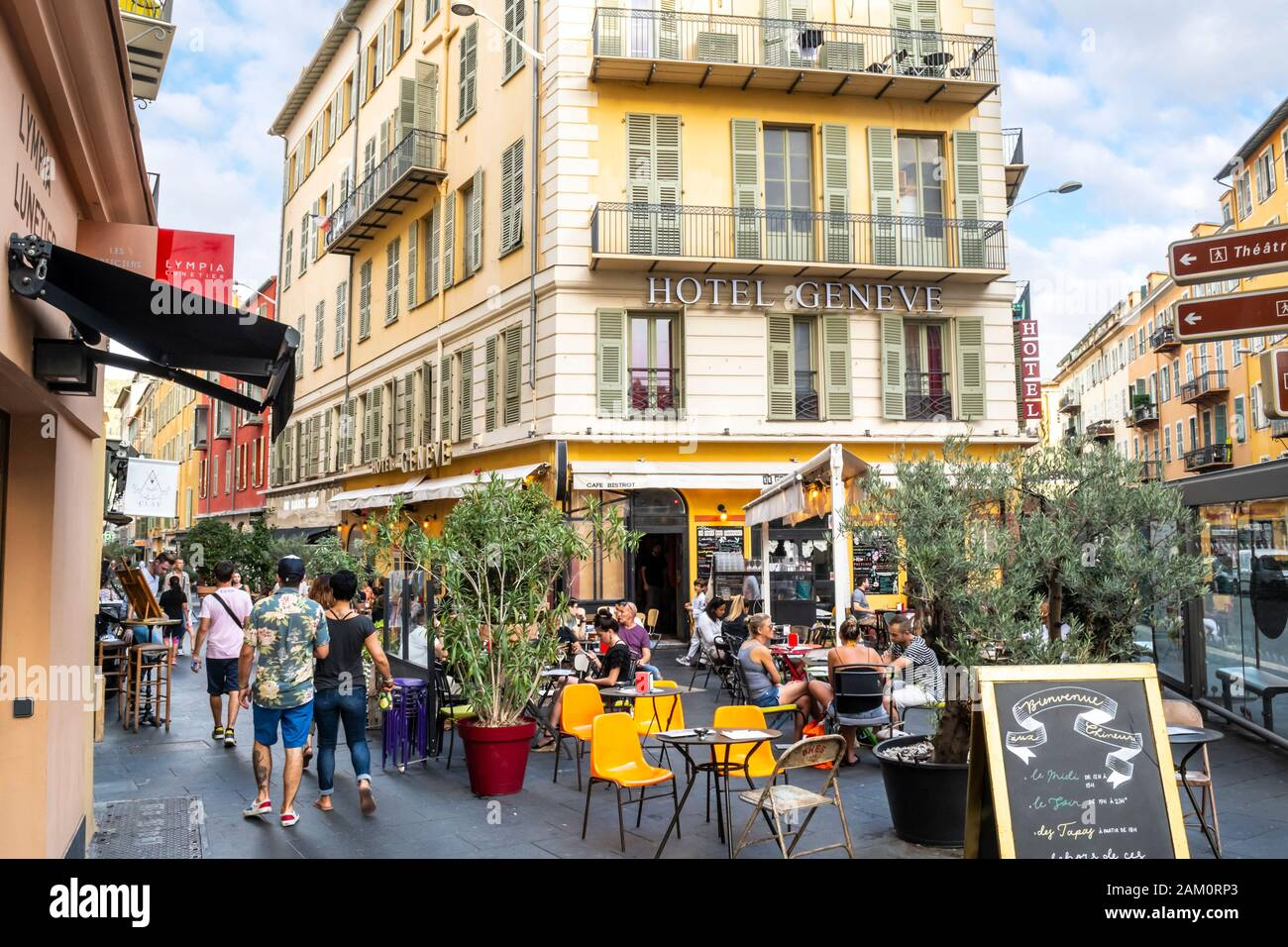 Tourists pass by the hotels, cafes and shops in the Old Town area of Nice, France, on the French Riviera. Stock Photo