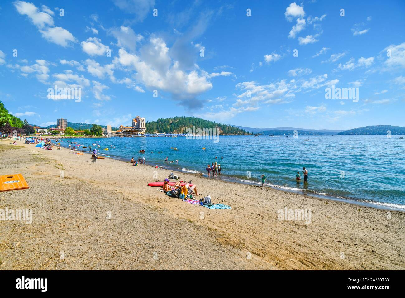 Tourists enjoy a sunny day at the beach of Independence Point at Lake Coeur d'Alene, in the mountain resort city of Coeur d'Alene, Idaho. Stock Photo