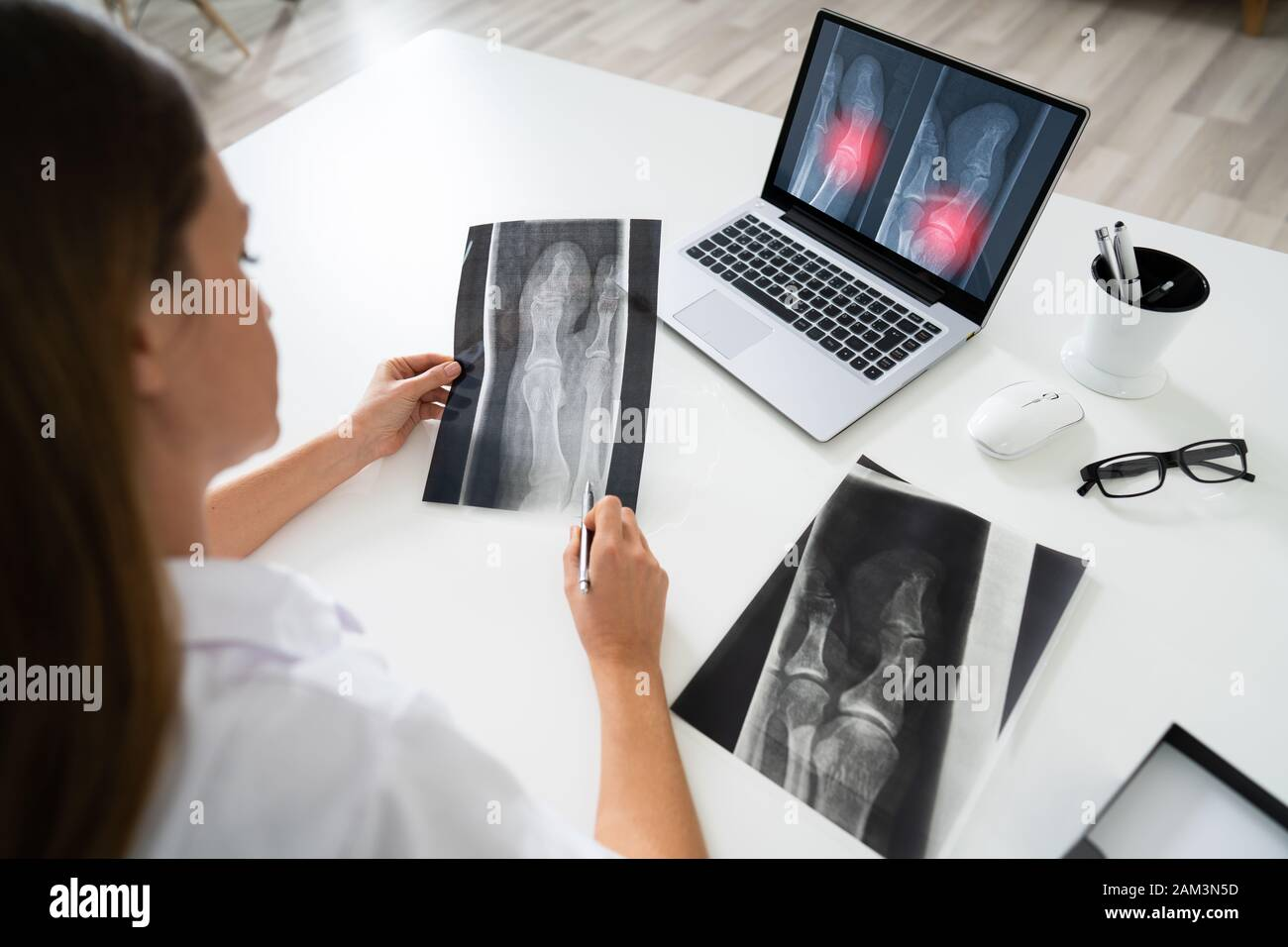 Female Doctor Examining Knee X-ray On Laptop In Clinic Stock Photo