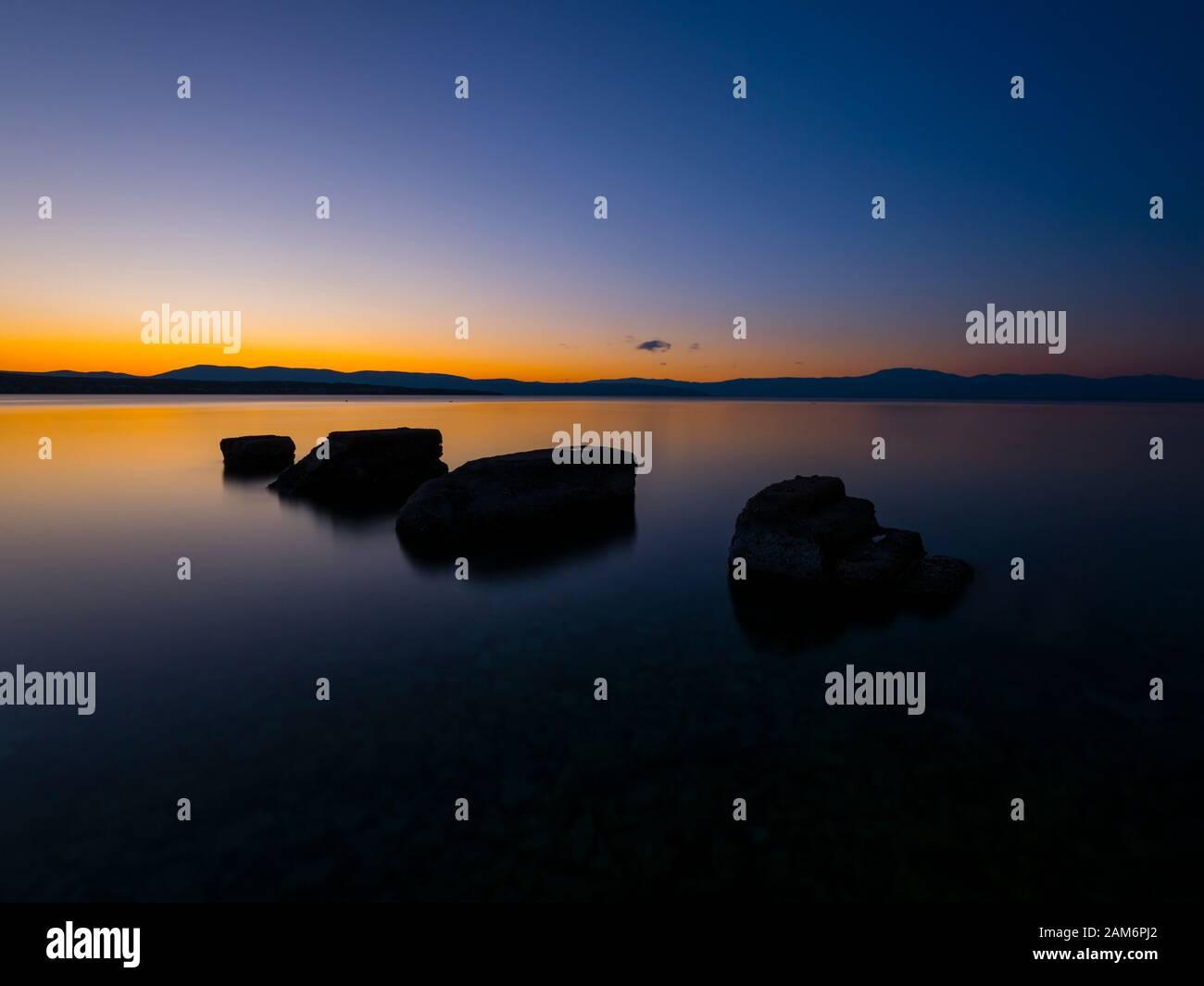 Sunset serene scenery rocks on calm sea surface Malinska on island Krk in Croatia Europe Stock Photo