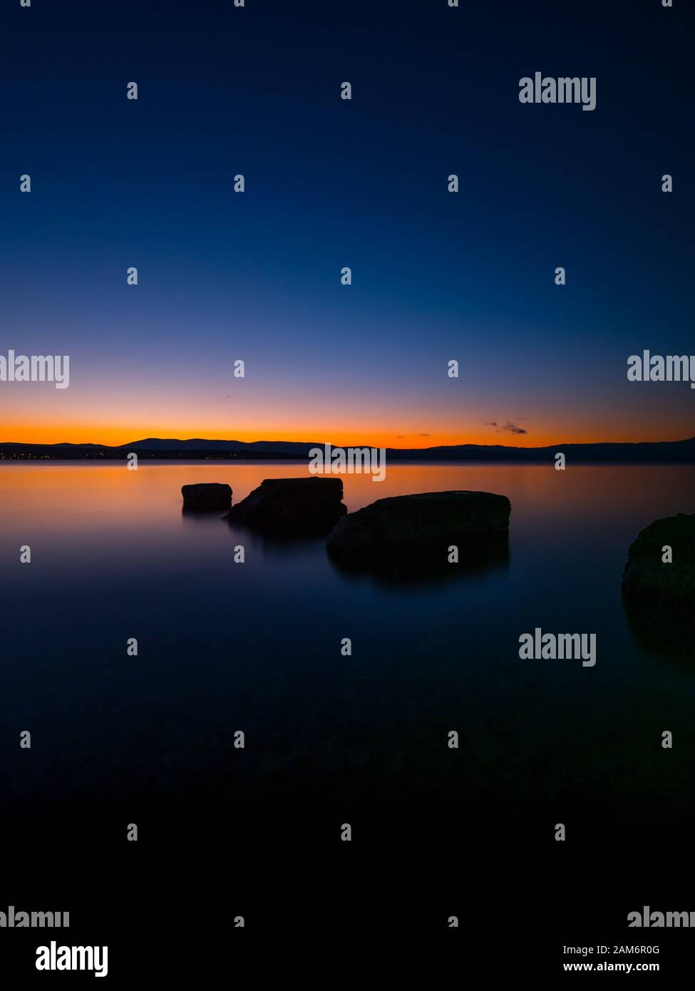 Sunset serene scenery rocks protruding from calm sea surface Malinska on island Krk in Croatia Europe Stock Photo