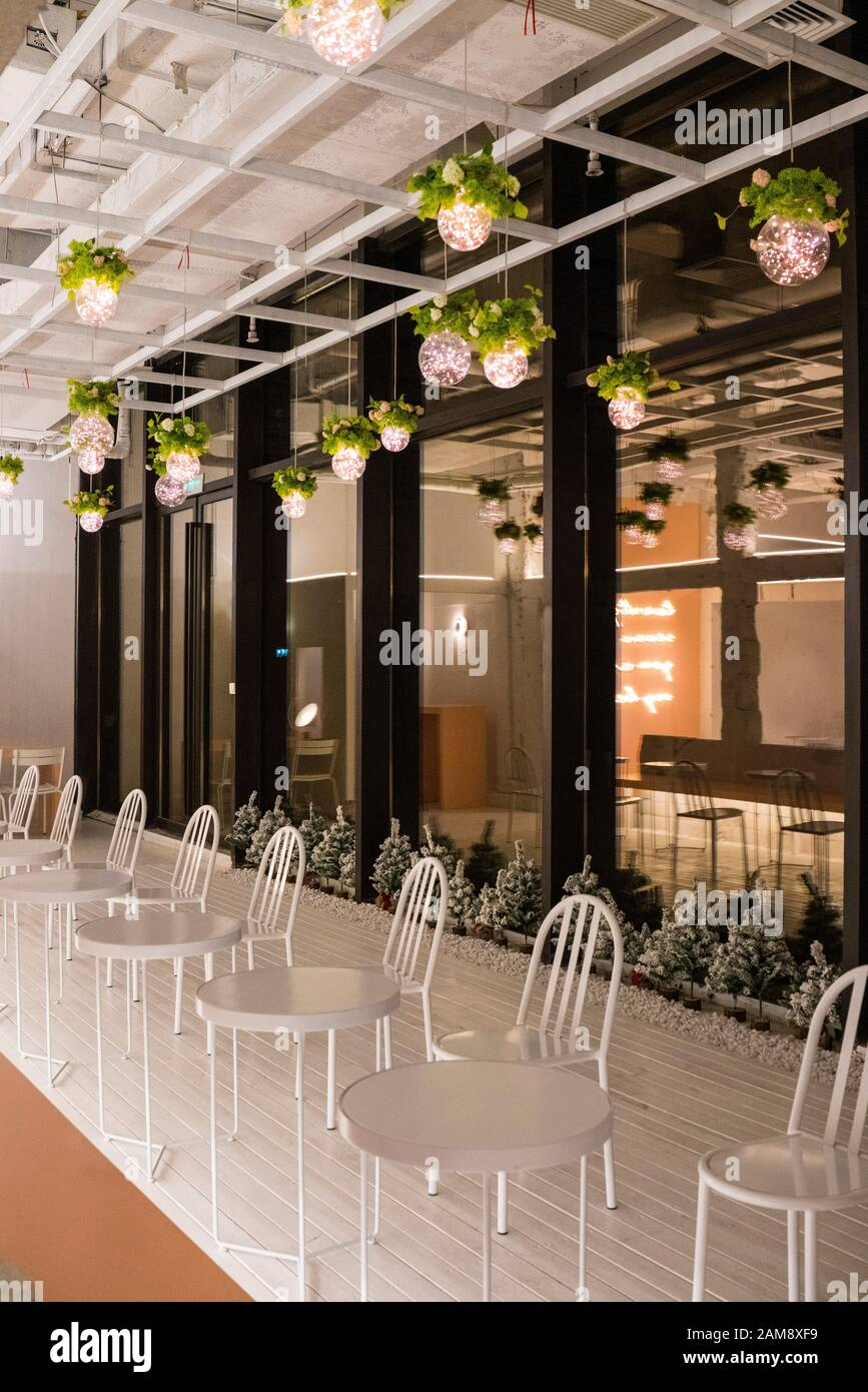 Interior Decoration White Chairs And Circle Desks Lamps With Leaves Are Hanging On The Ceiling Stock Photo Alamy