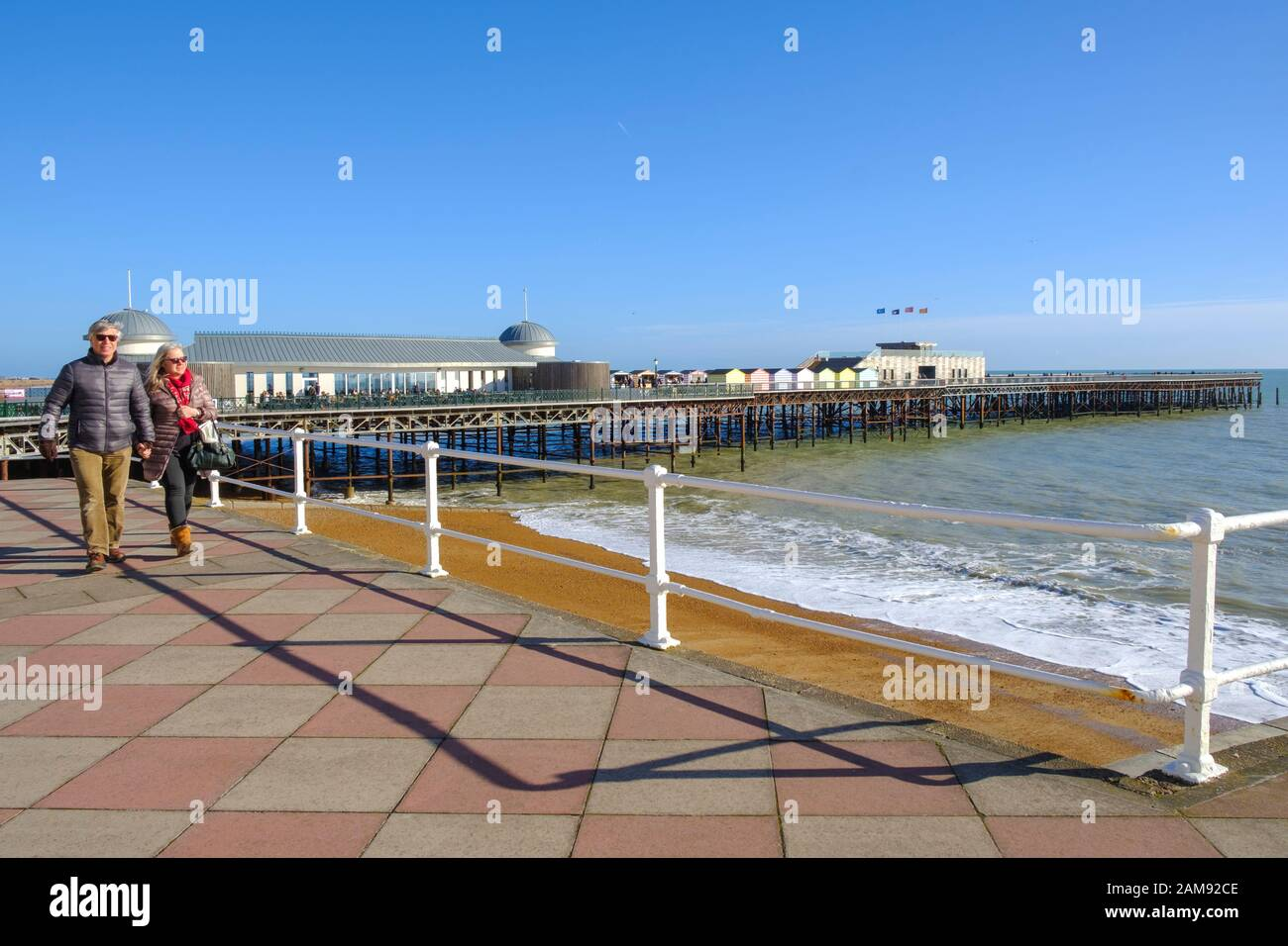 Couple strolling along Hastings seafront promenade in front of the pier; under cloudless skies, on a sunny winter day, East Sussex, UK Stock Photo