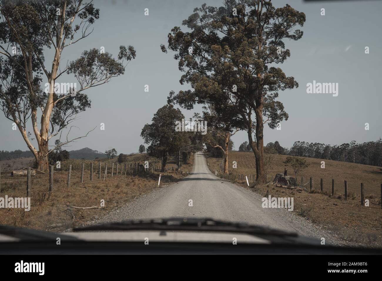 Looking down a country gravel road in farmland Comboyne, New South ...