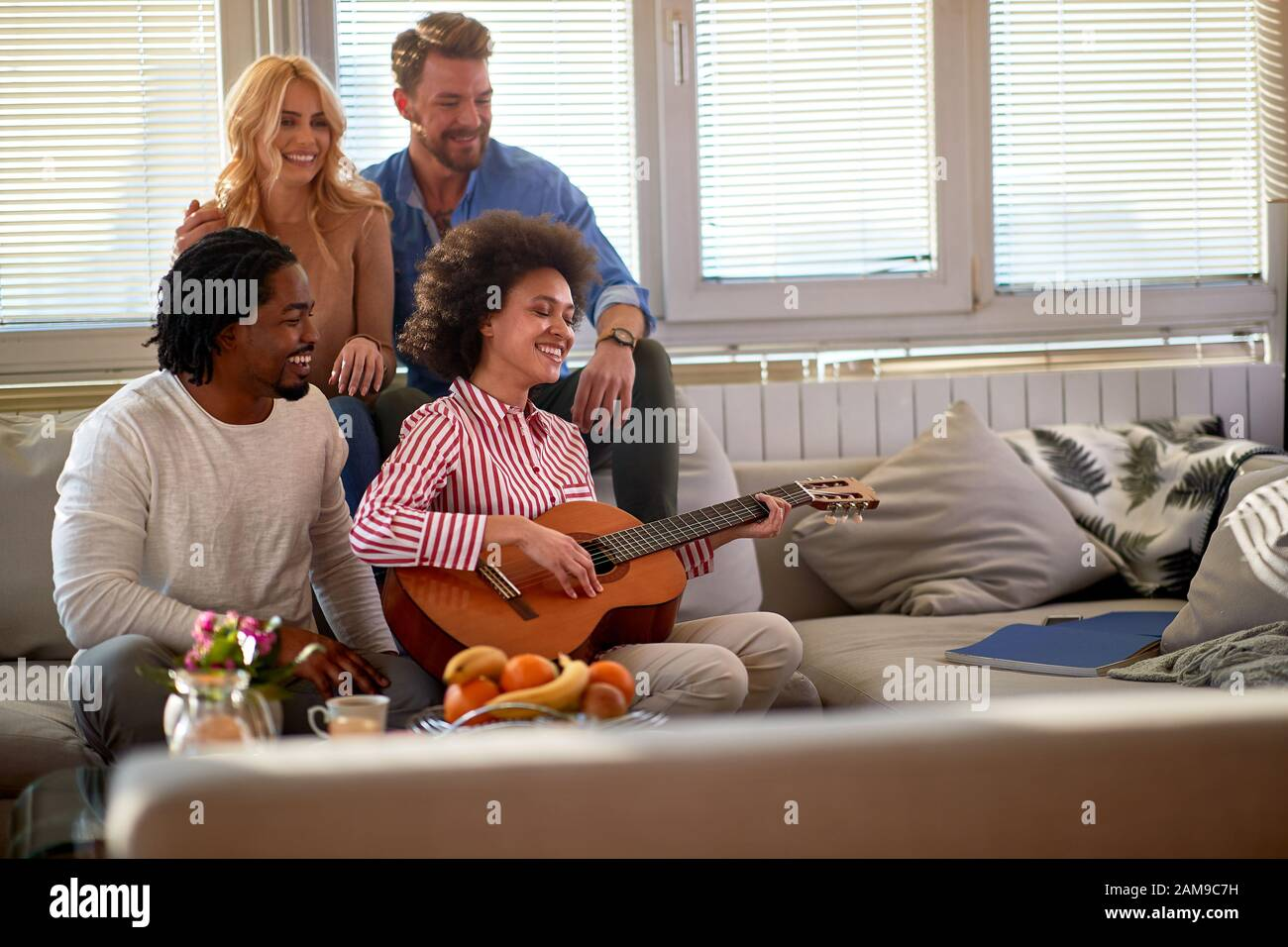 Young woman play guitar end hang out with friends Stock Photo