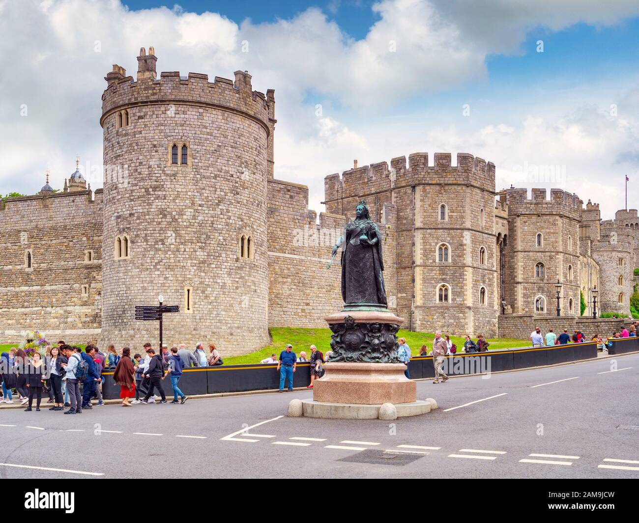 5 June 2019: Windsor, Berkshire, UK - Windsor Castle, the Queen's home, street scene with statue of Queen Victoria, tourists and tour group. Stock Photo