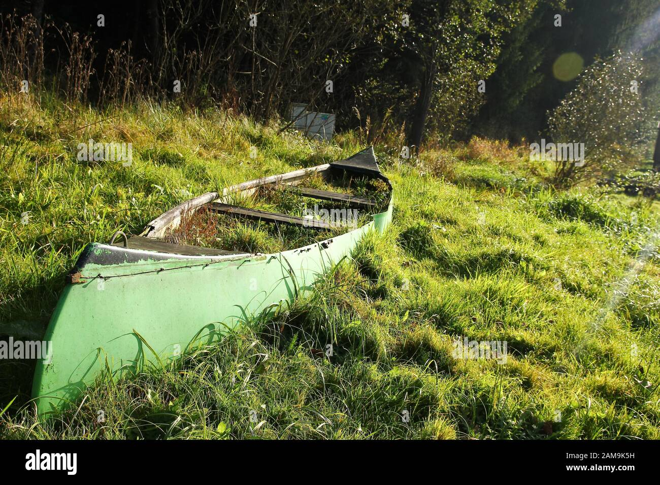 The old canoe is lying on the meadow close to the river and is abandoned, fully overgrown by grass and useless. Stock Photo