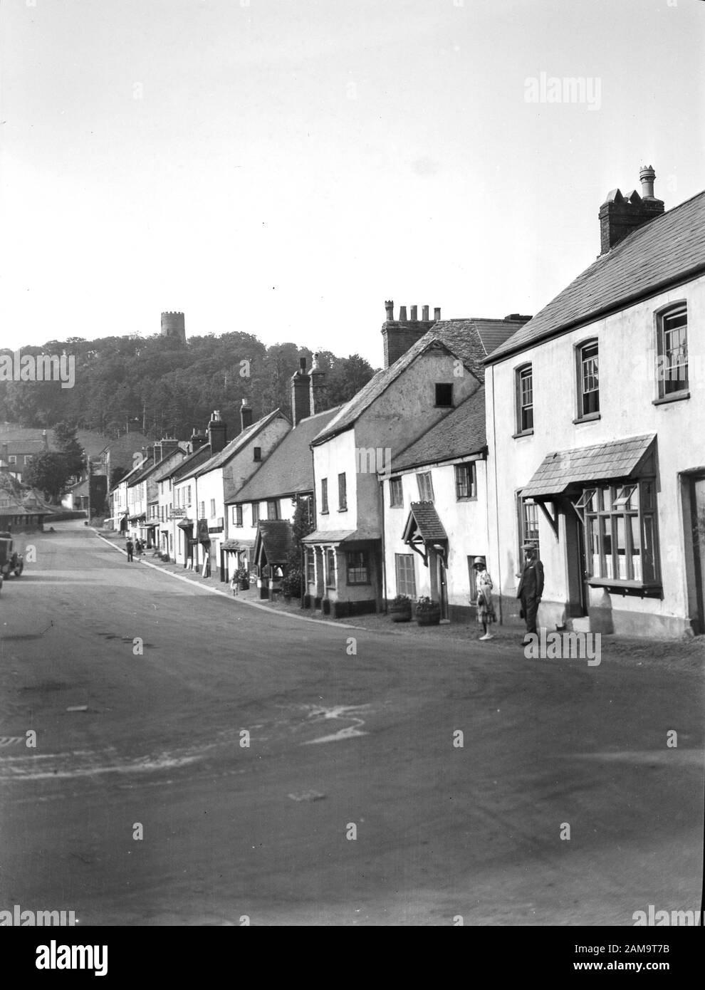 Archive image circa 1920s of Dunster High Street, Somerset, UK, showing Conygar Tower and  Lock Tea rooms. Scanned from original glass negative. Stock Photo