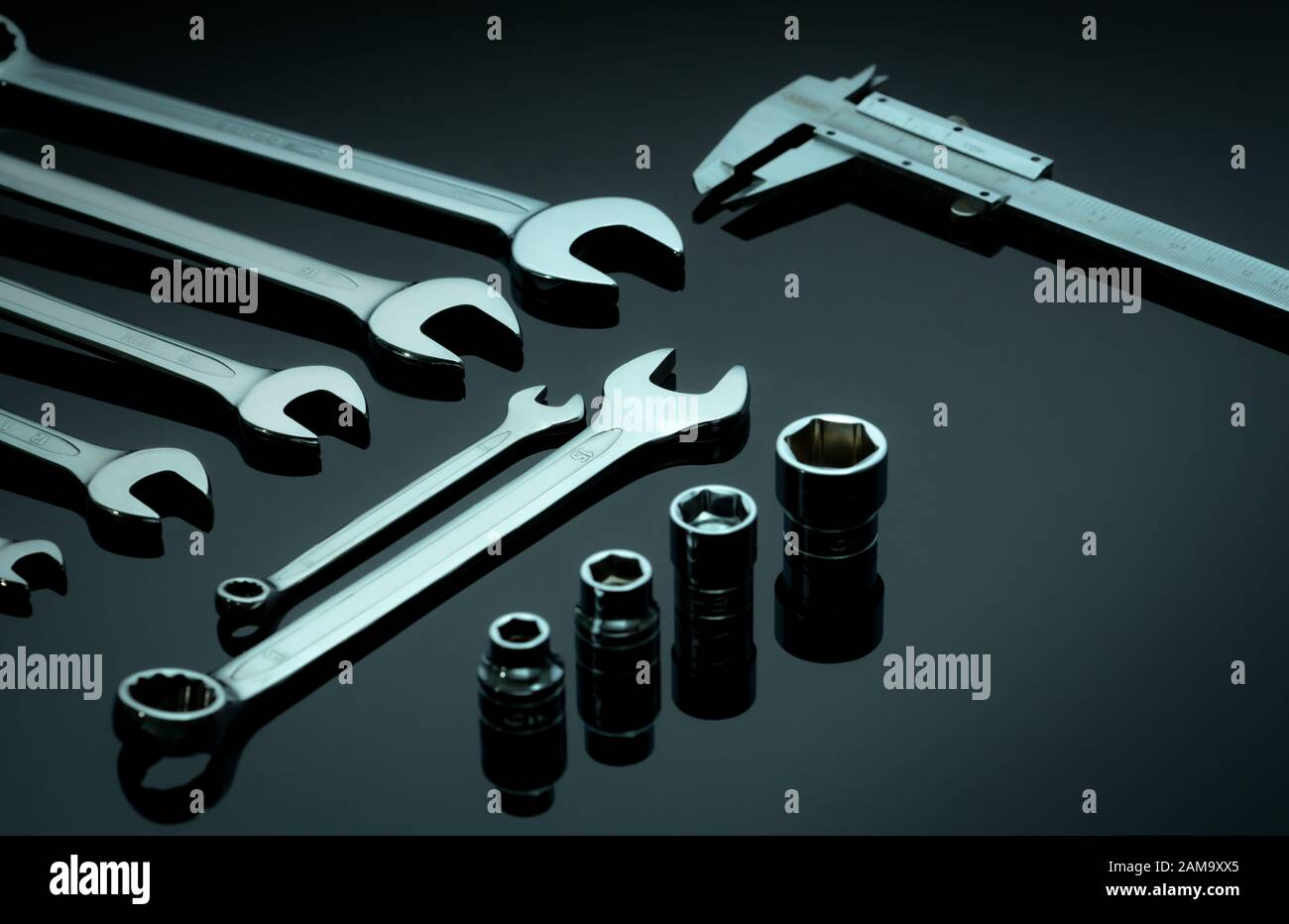 Set of chrome wrenches or spanners, hexagon socket, and vernier caliper on dark table in workshop. Chrome vanadium spanner wrench. Silver wrenches. Stock Photo