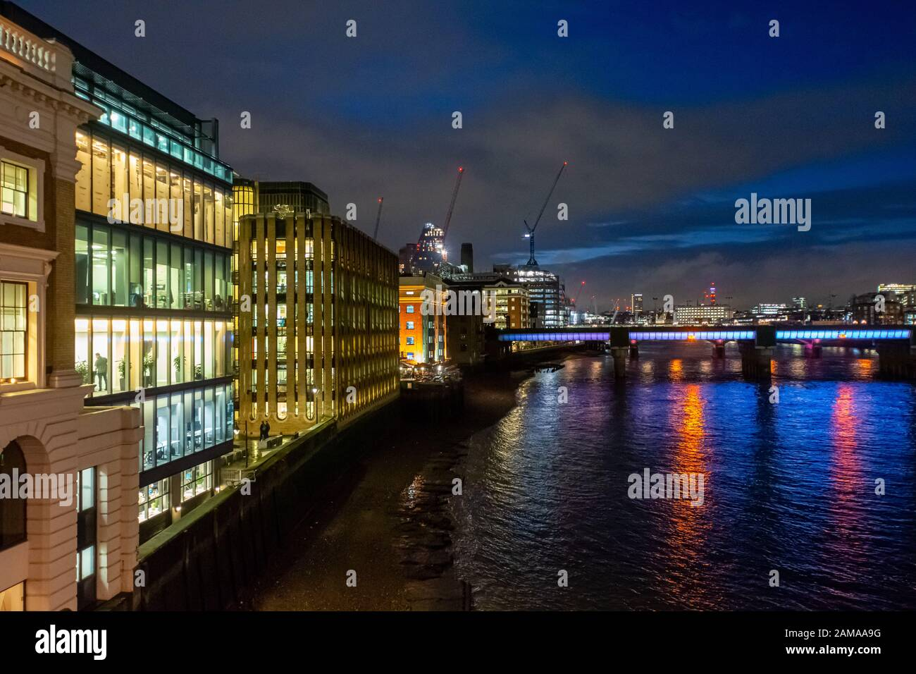 Looking west from London Bridge along the River Thames towards Cannon Street Railway Bridge at night with illuminated offices on the South Bank, UK Stock Photo