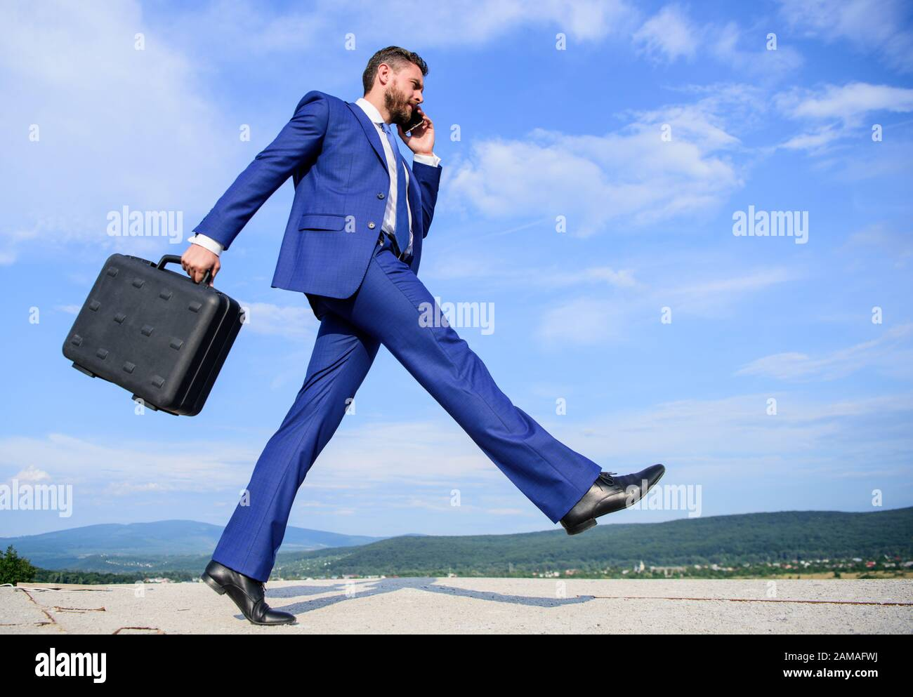 Businessman formal suit carries briefcase sky background. Businessman solving business problems on phone. Never stop. Keep going towards your goal. Entrepreneur in motion purposeful expression. Stock Photo