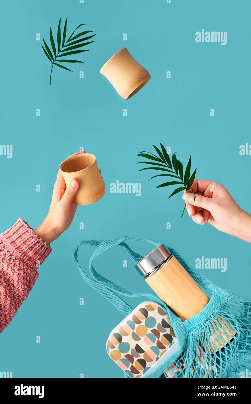 Zero waste tea in in eco friendly insulated bamboo flask. Two hands with cup and palm leaf, net bag with lunch box and tea flask are flying. Zero wast Stock Photo