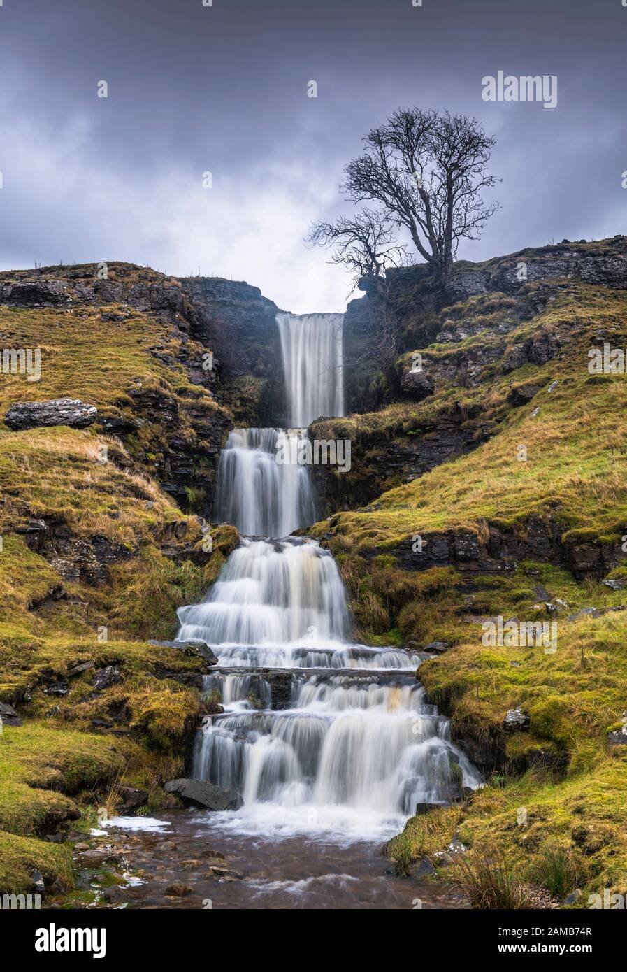 Standing in a rain & hail storm photographing the stunning cascading terraces of Cow Gill Waterfalls in Cray, Yorkshire Dales National Park. Stock Photo