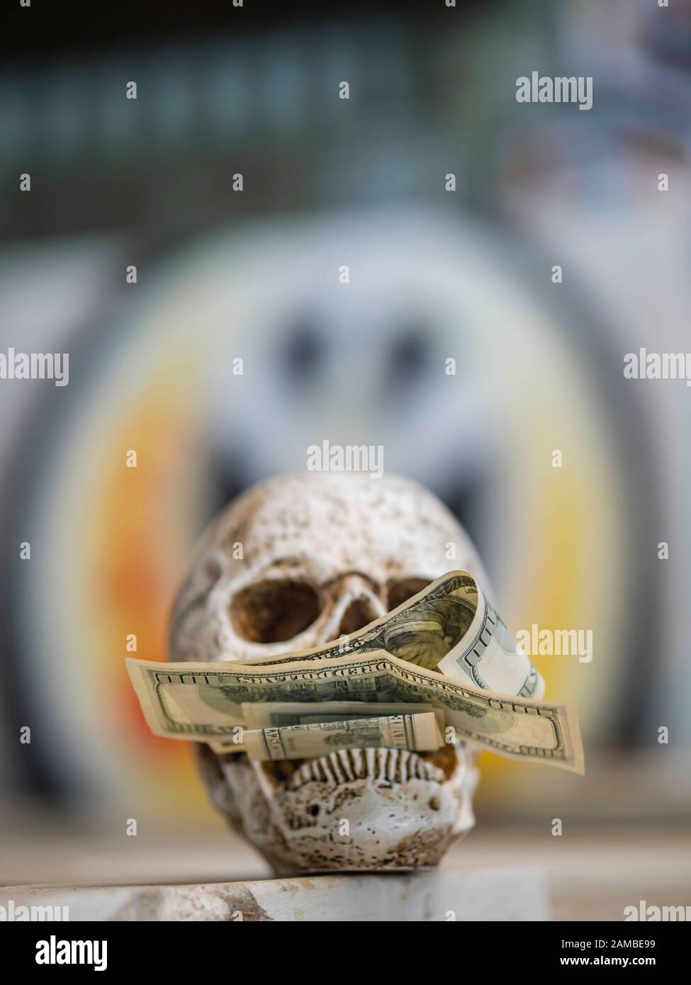 Human skull holding money peace sign spray painted on background graffiti on wall greed for wealth Stock Photo