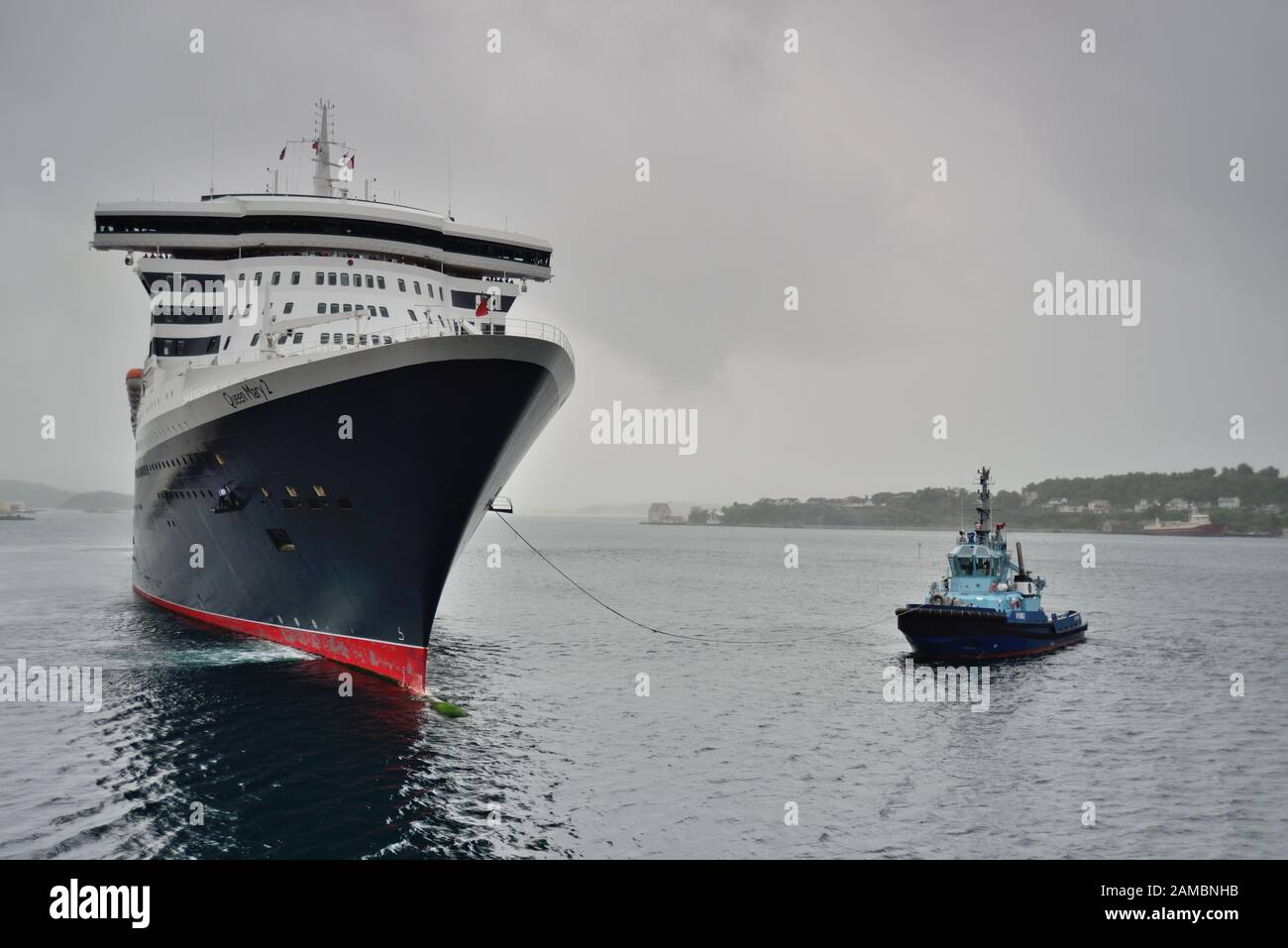 Cunard liner Queen Mary II being assisted by a tug boat as it leaves the dockside at Alesund on a wet and overcast day. Stock Photo