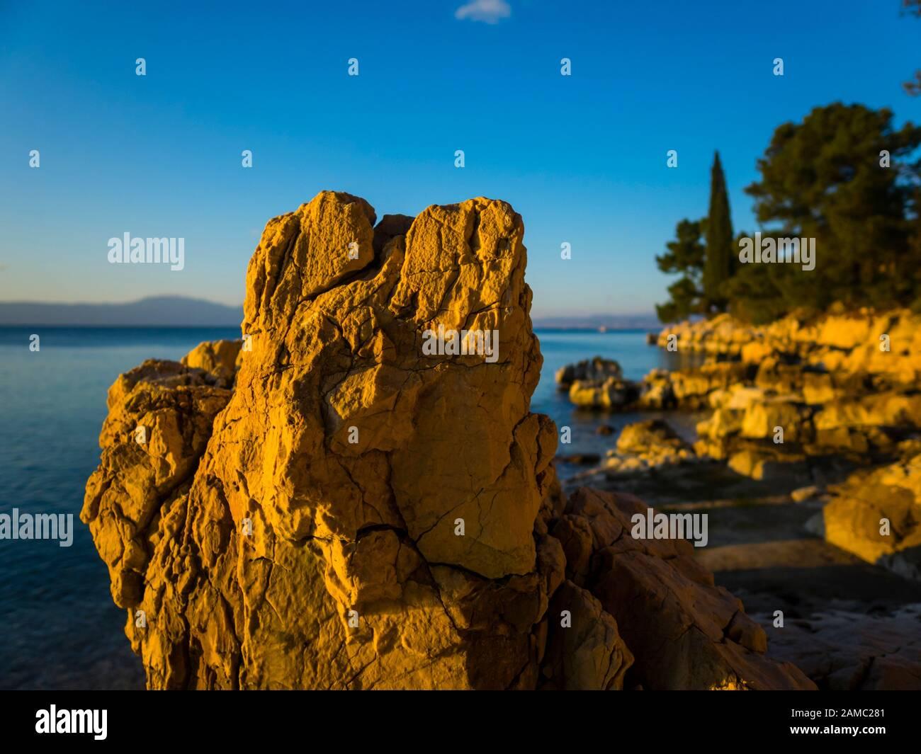 Sunset lighted light on boulder rock on beach seaside Malinska on island Krk in Croatia Europe Stock Photo