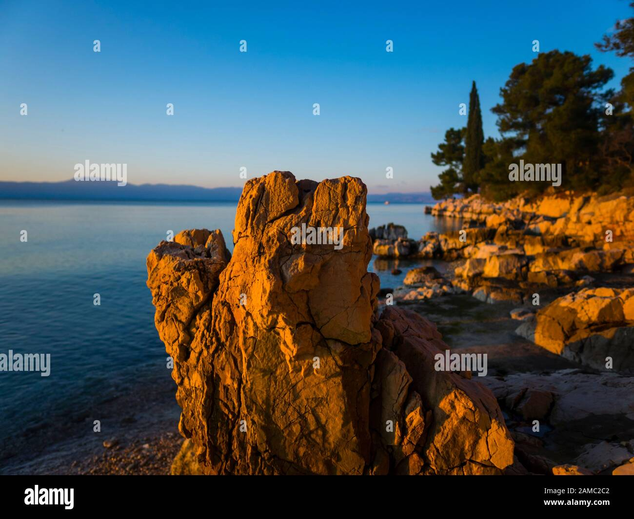 Sunset lighted light on boulder rock on beach seaside before coastline promenade Malinska on island Krk in Croatia Europe Stock Photo