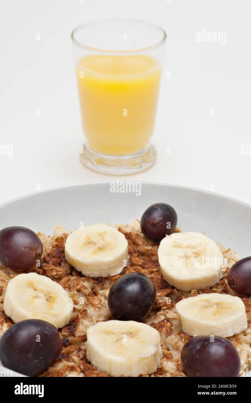Healthy Low Fat Breakfast Of Hot Oatmeal Banana Slices And Blueberries In White Bowl Stock Photo Alamy