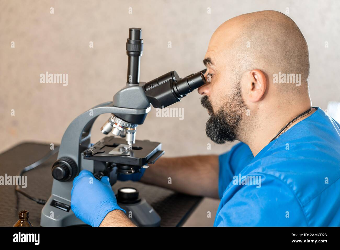 Male laboratory assistant examining biomaterial samples in a microscope. Stock Photo