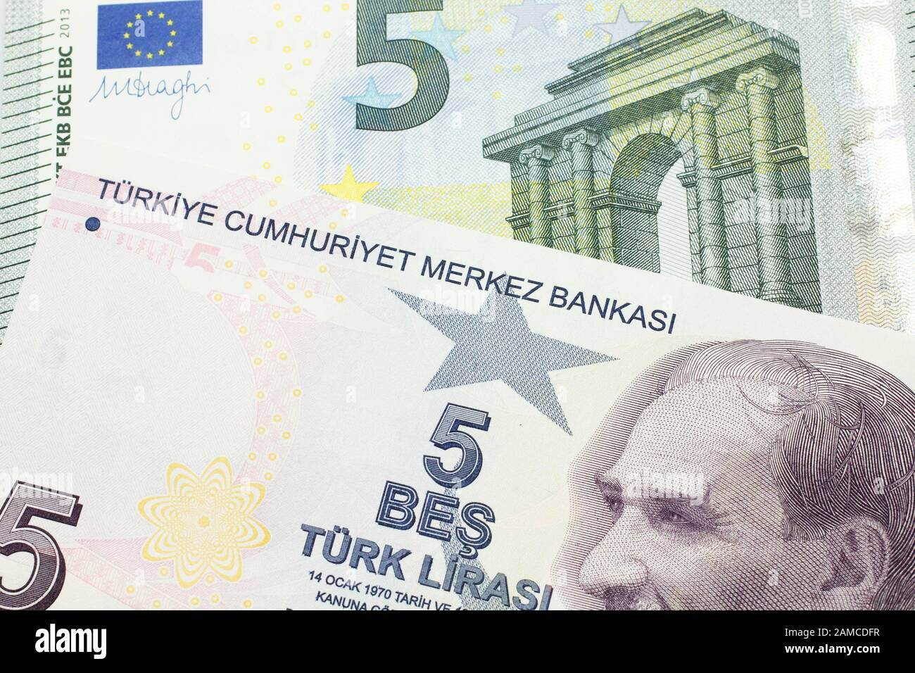 A close up image of a purple five Turkish lira bank note with a German five euro bill in macro Stock Photo