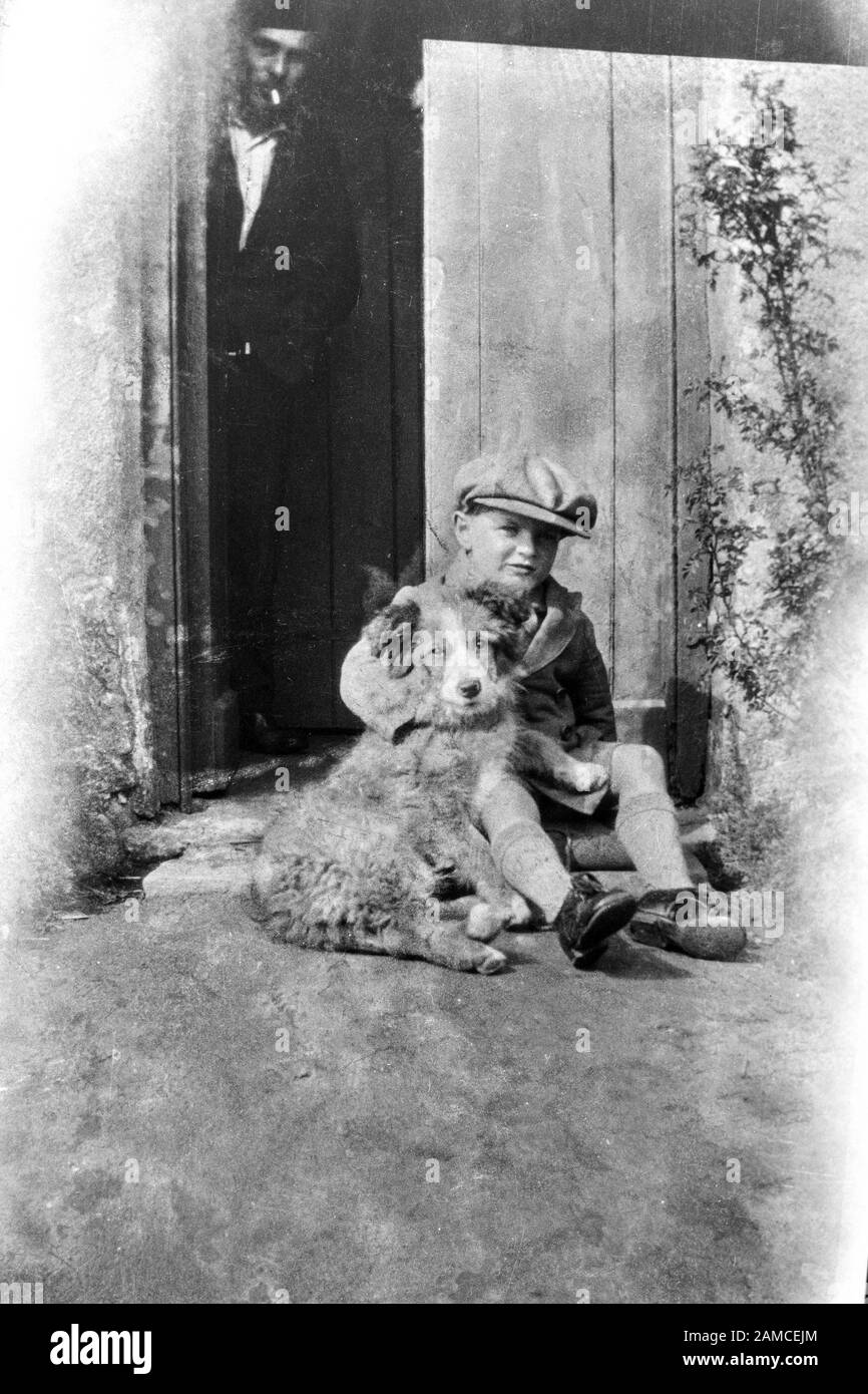 Archive image of a young boy hugs his dog, while a man watches from a doorway, circa 1910-1920 scanned directly from the negative Stock Photo
